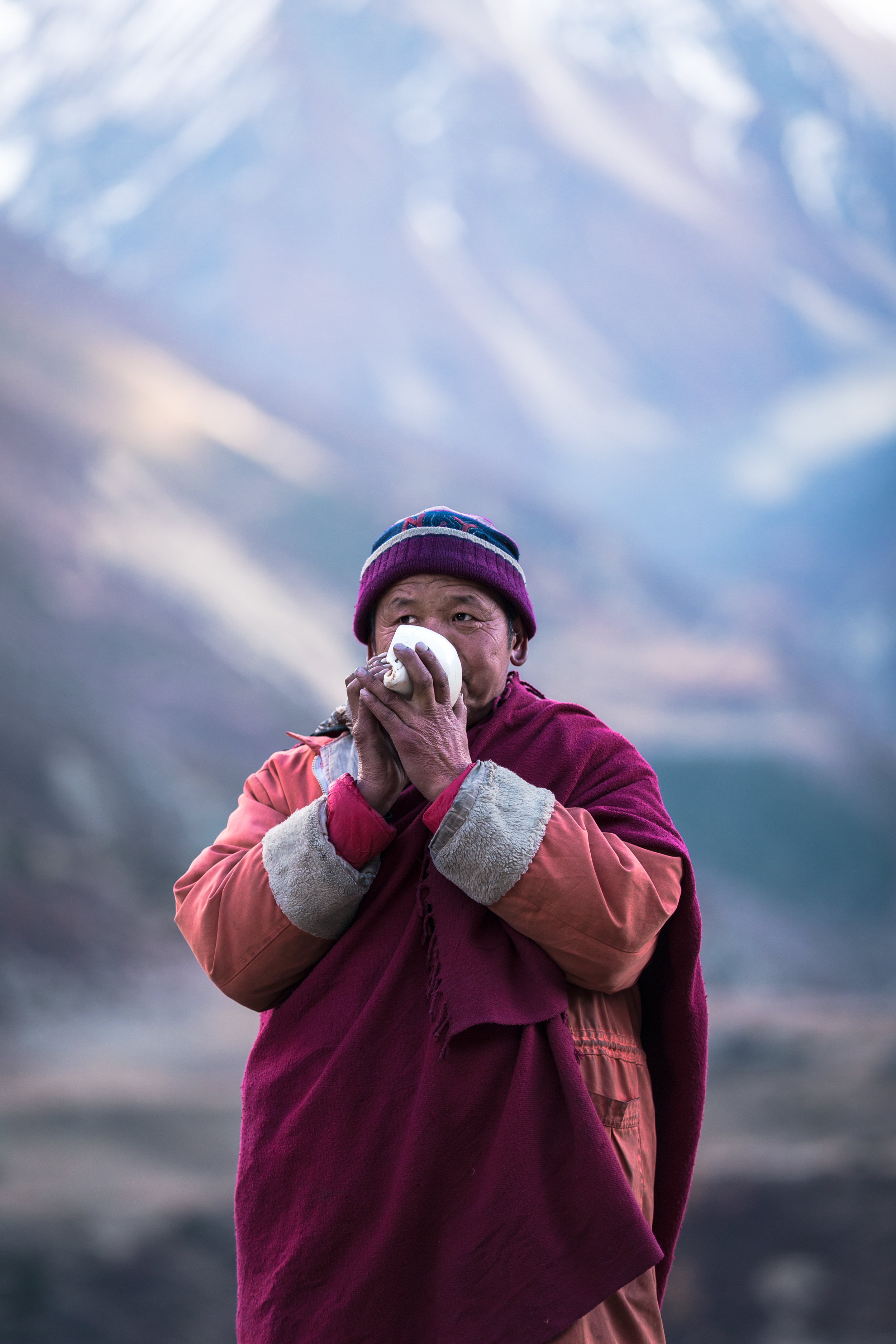 A monk blows into a conch shell at the monastery in Mu Gompa.
