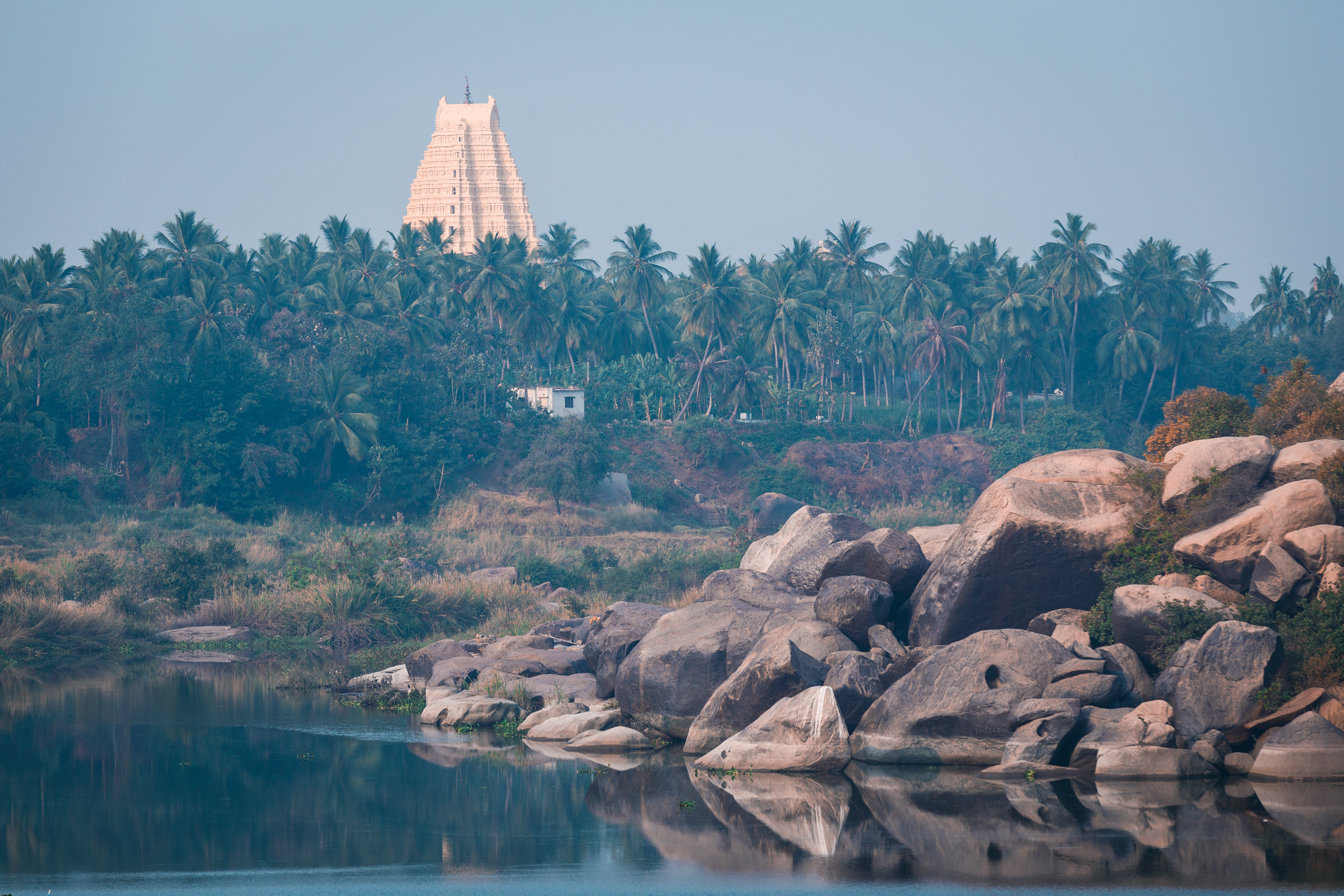 Across the Tungabhadra River lies the Virupaksha Temple dedicated to Lord Shiva, standing tall over the ruins of Hampi.