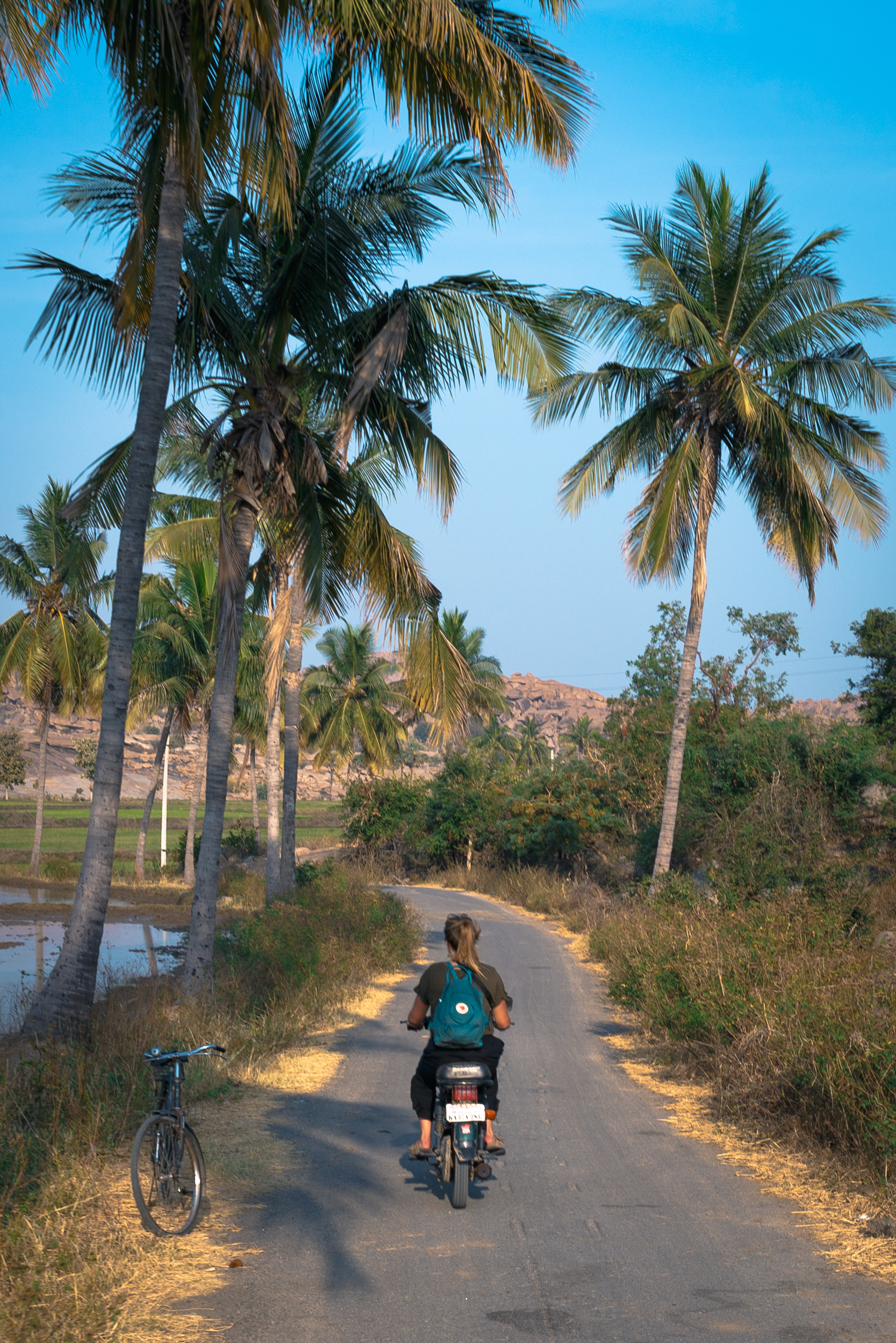 Riding on a motorbike through the rice paddies on Hampi Island.