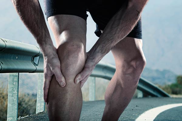 An athlete grips his injured leg in pain while running. Acupuncture can help.