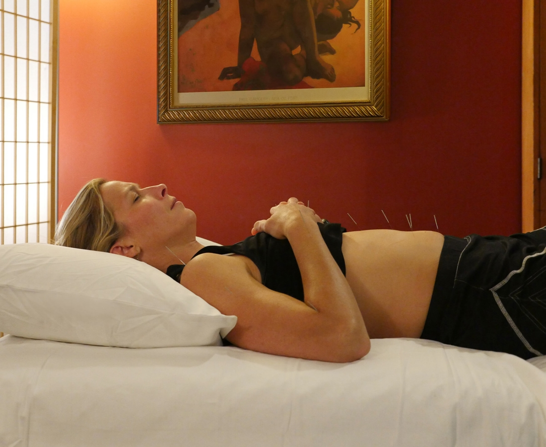 A woman dealing with female-specific health complaints rests peacefully in a comfortable room during an acupuncture treatment