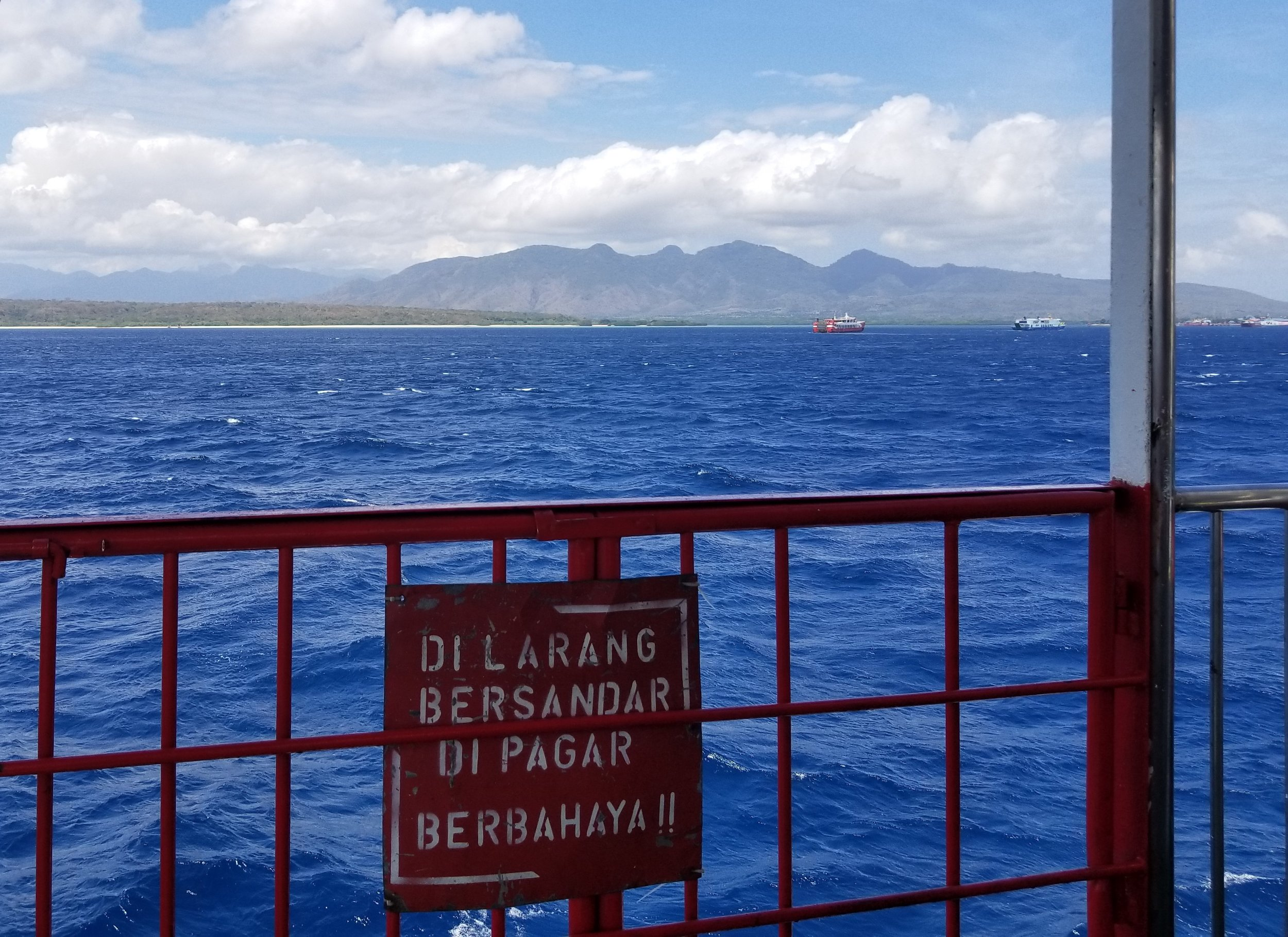 View of Bali from the ferry with impossibly blue waters in the channel. Sign says not to lean on the rail