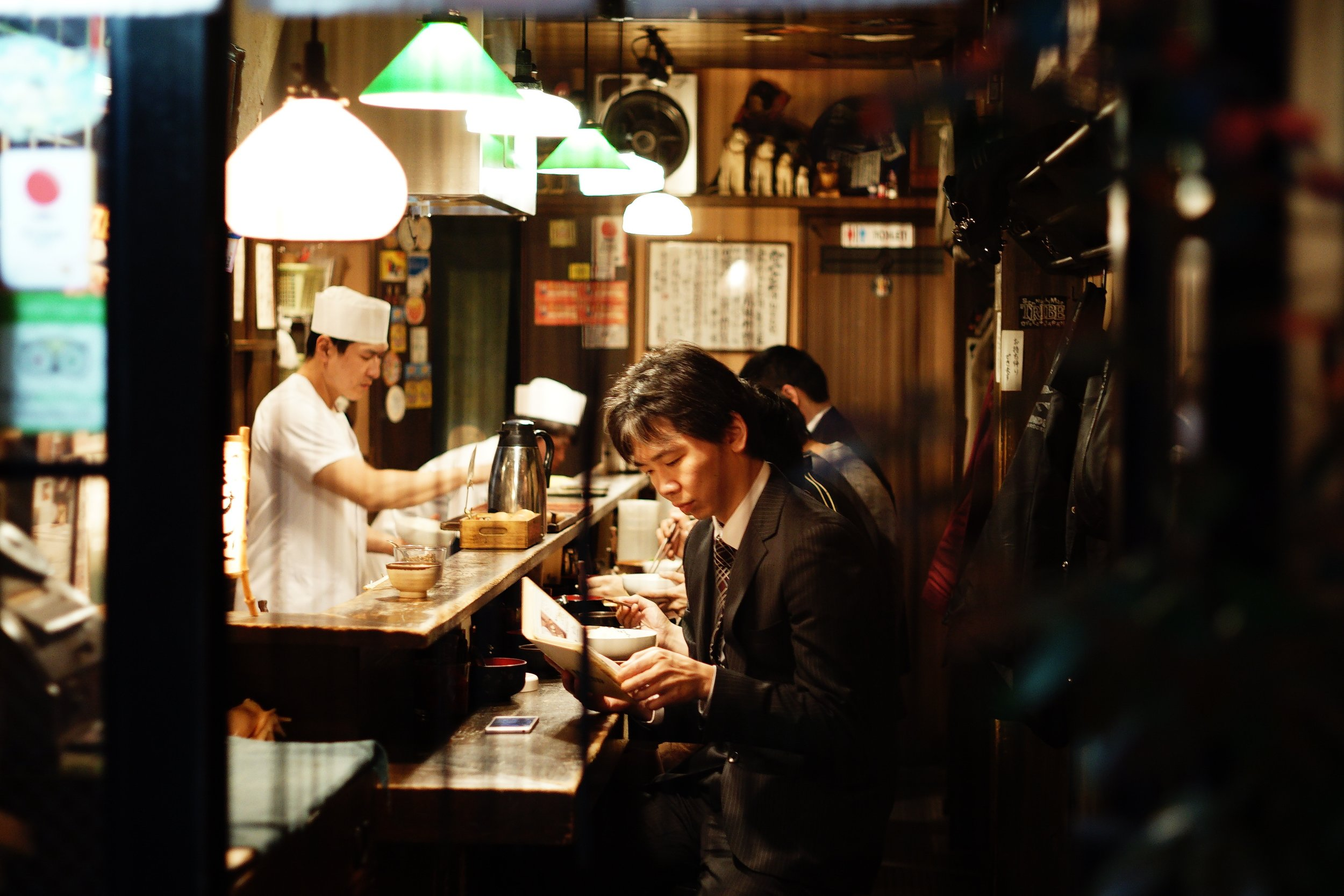 japanese man sits at a sushi bar in tokyo reading the menu