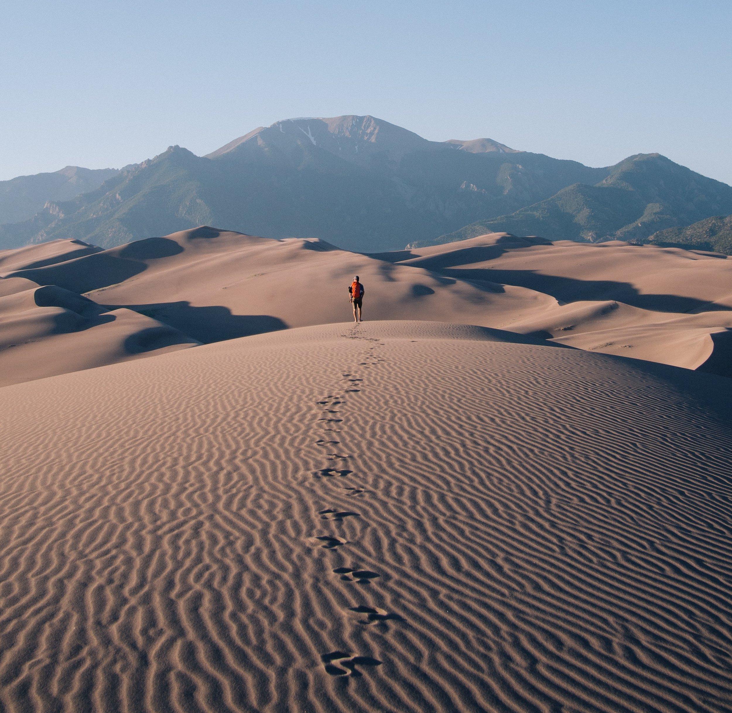 man walks on desert towards mountains leaving footprints in the sand.jpg