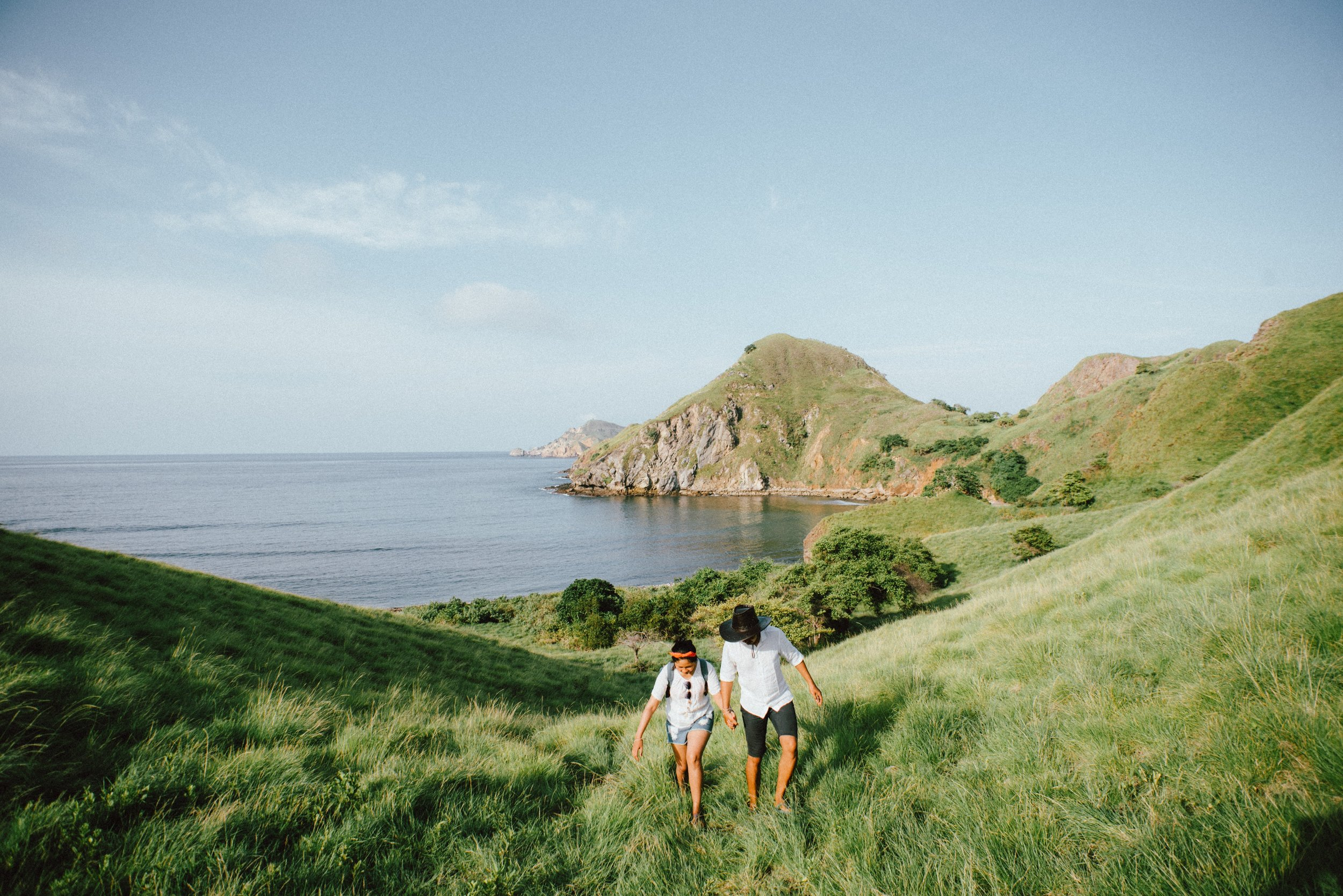 couple holding hands walking up a hill on serene coast.jpg