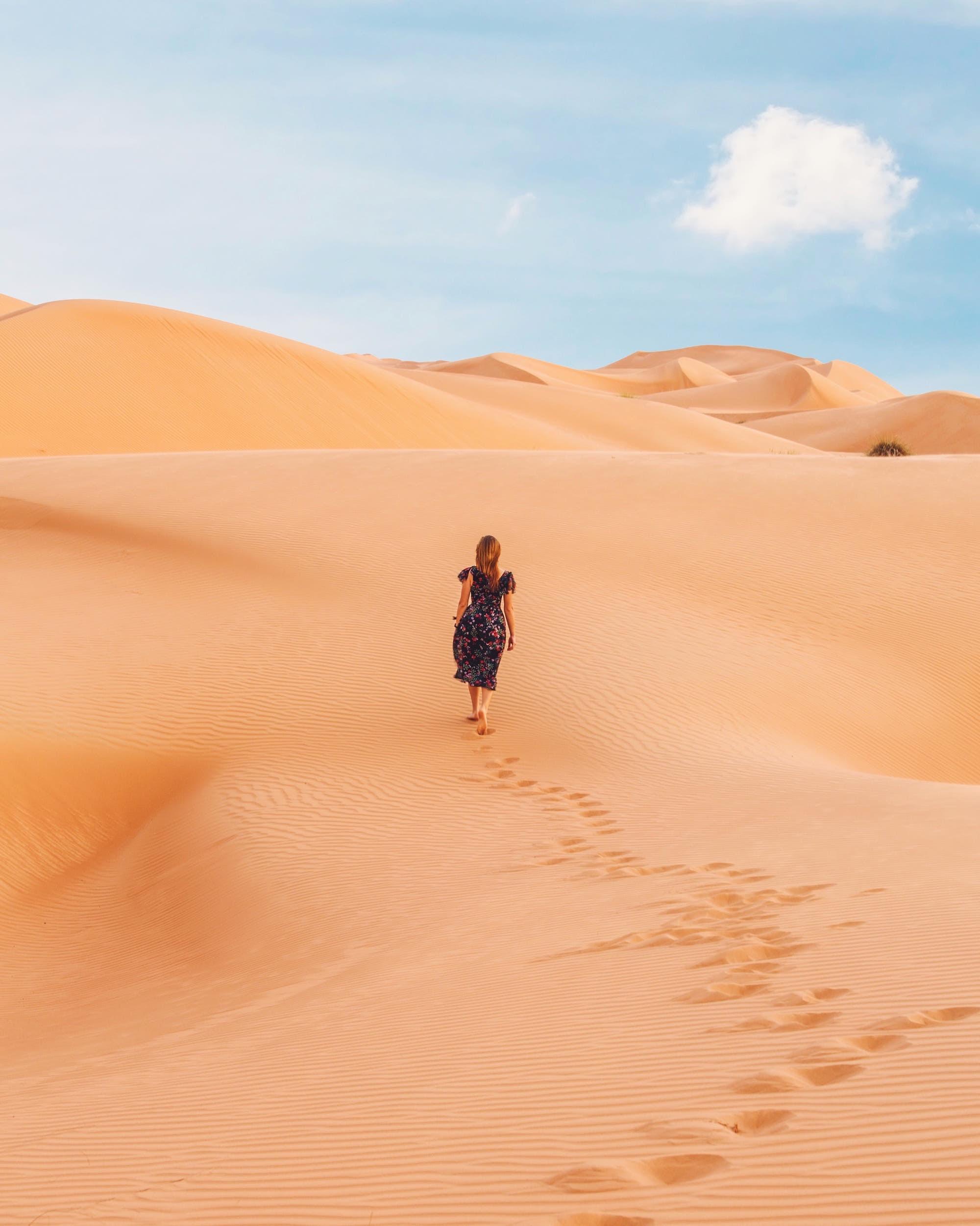woman solo wandering along the desert in Oman