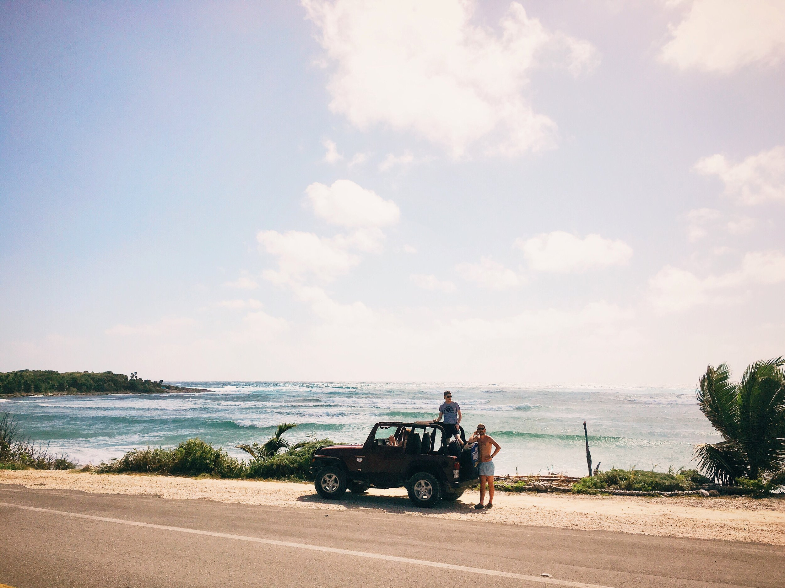 jeep parked on the side of a scenic seaside road with a group of friends