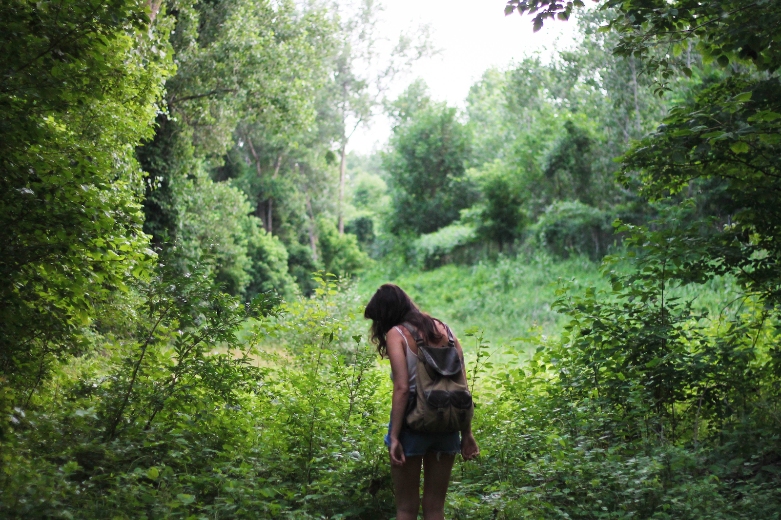 girl with backpack stepping into unkown forest discovering something new.png