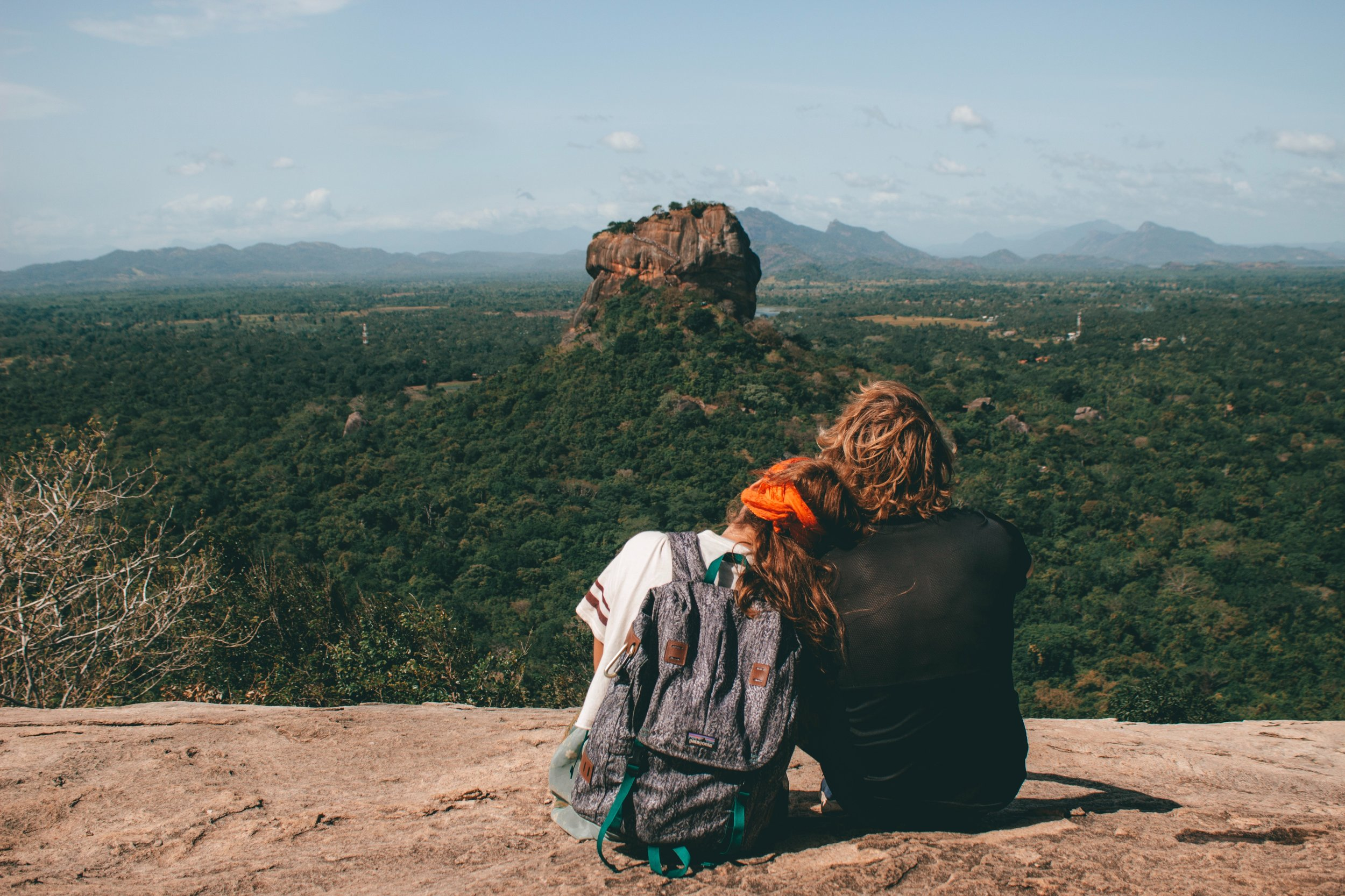 couple looking at rocks surrounded by forest in the distance with beautiful scenery