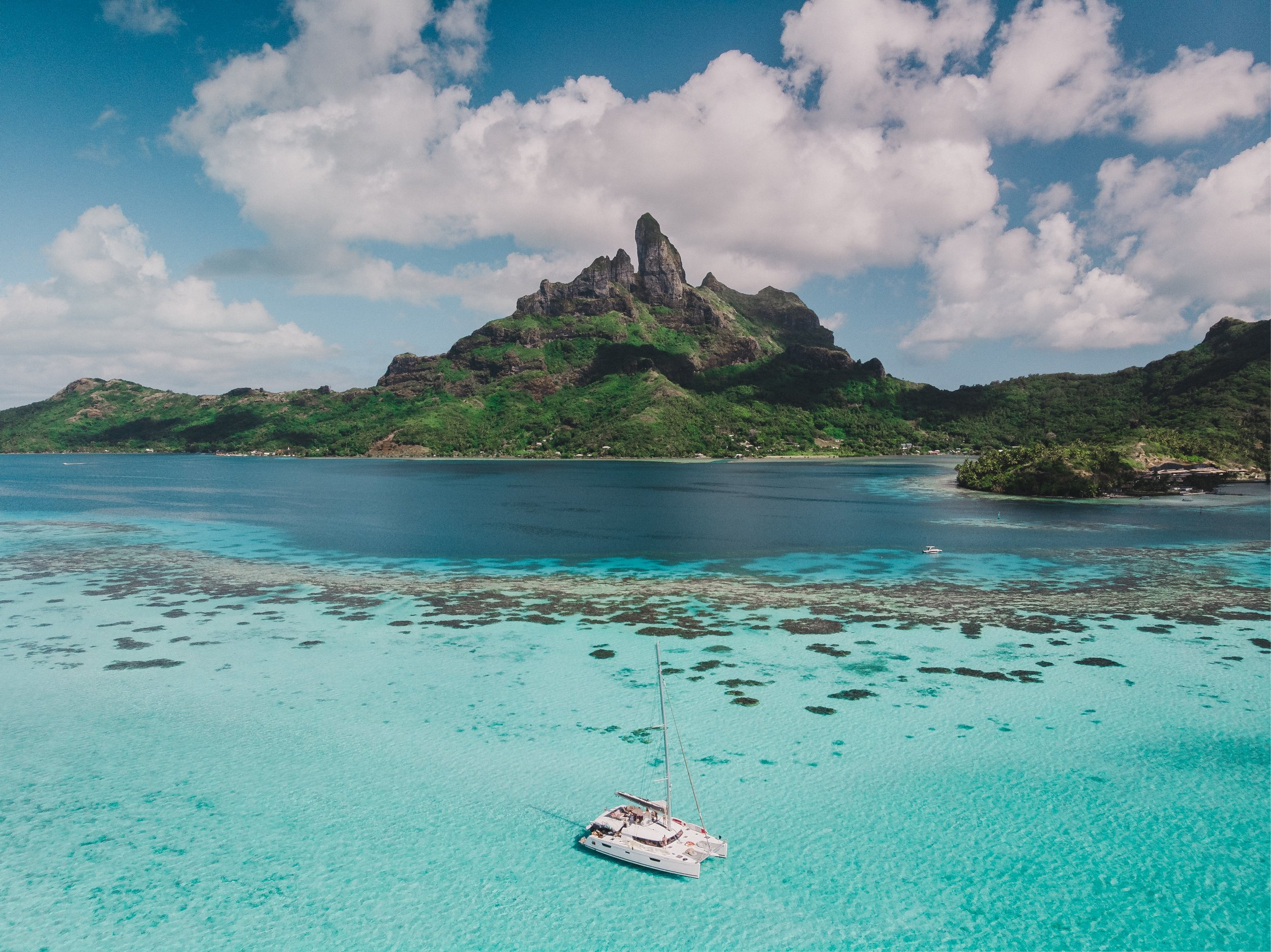 sailboat in paradiscal water by a rocky island in bora bora