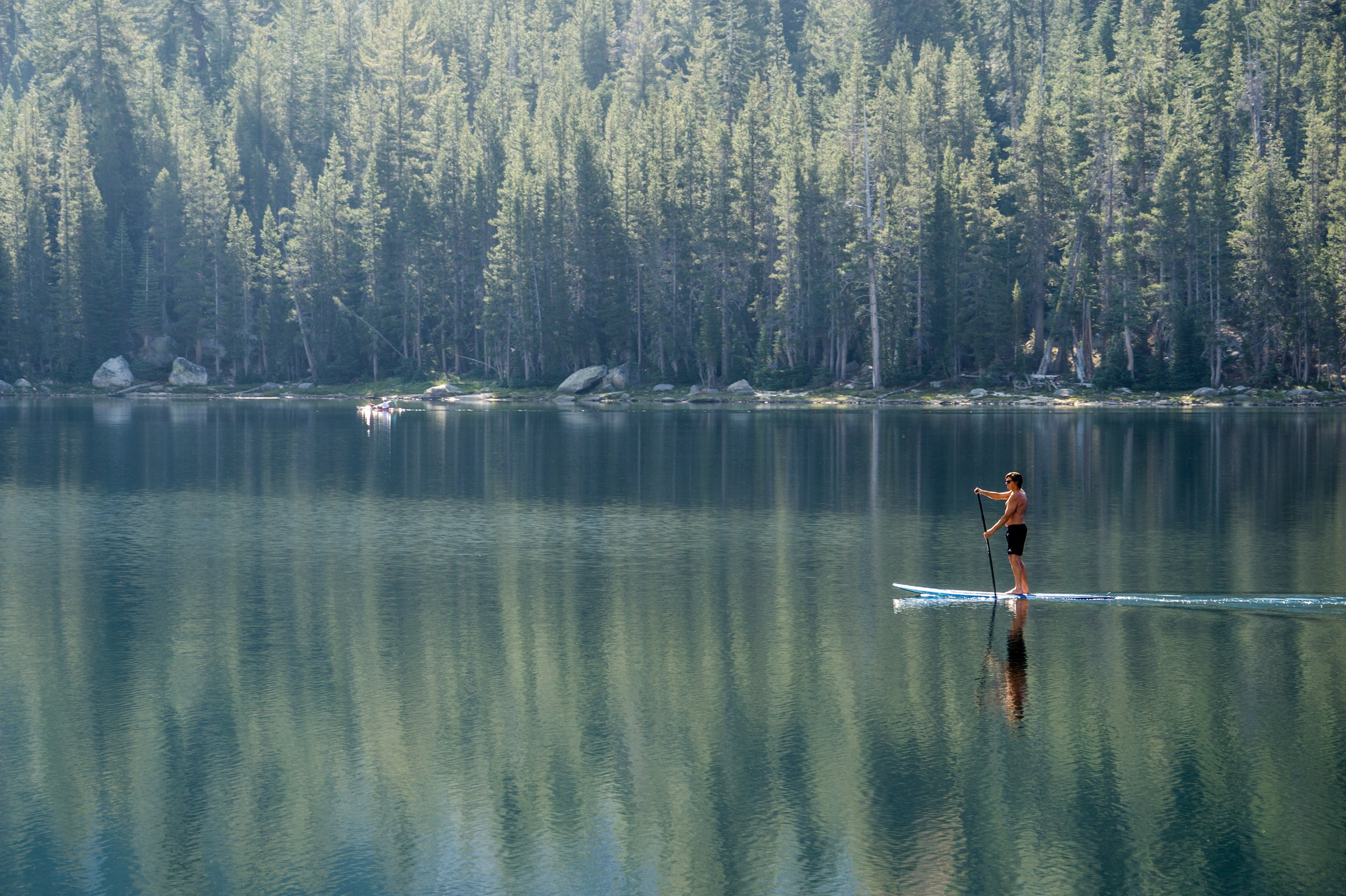 man paddling through still lake by a forest