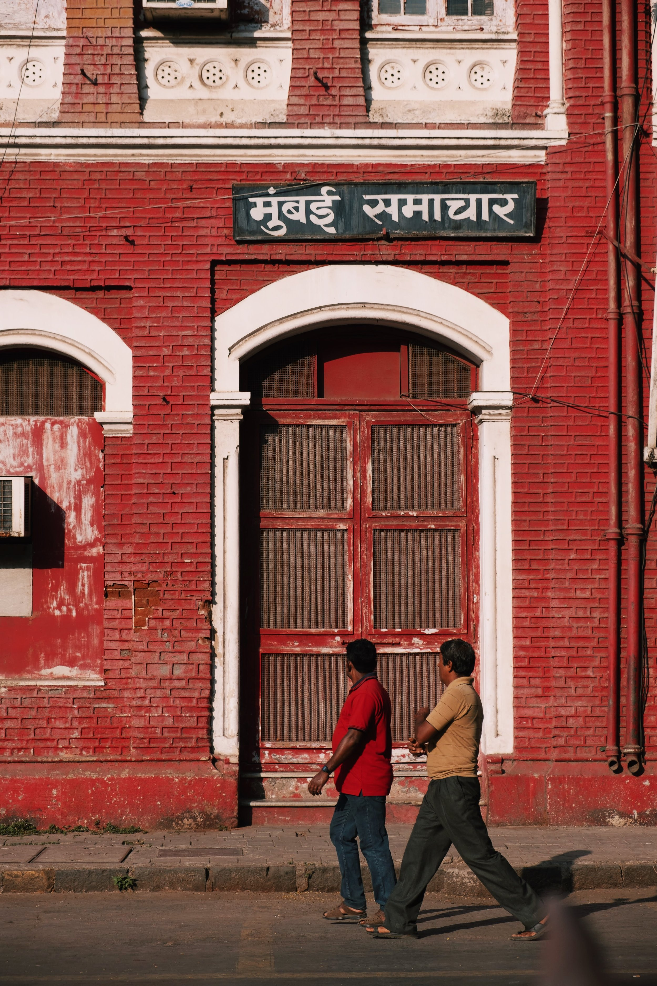 people walking past a red building in India