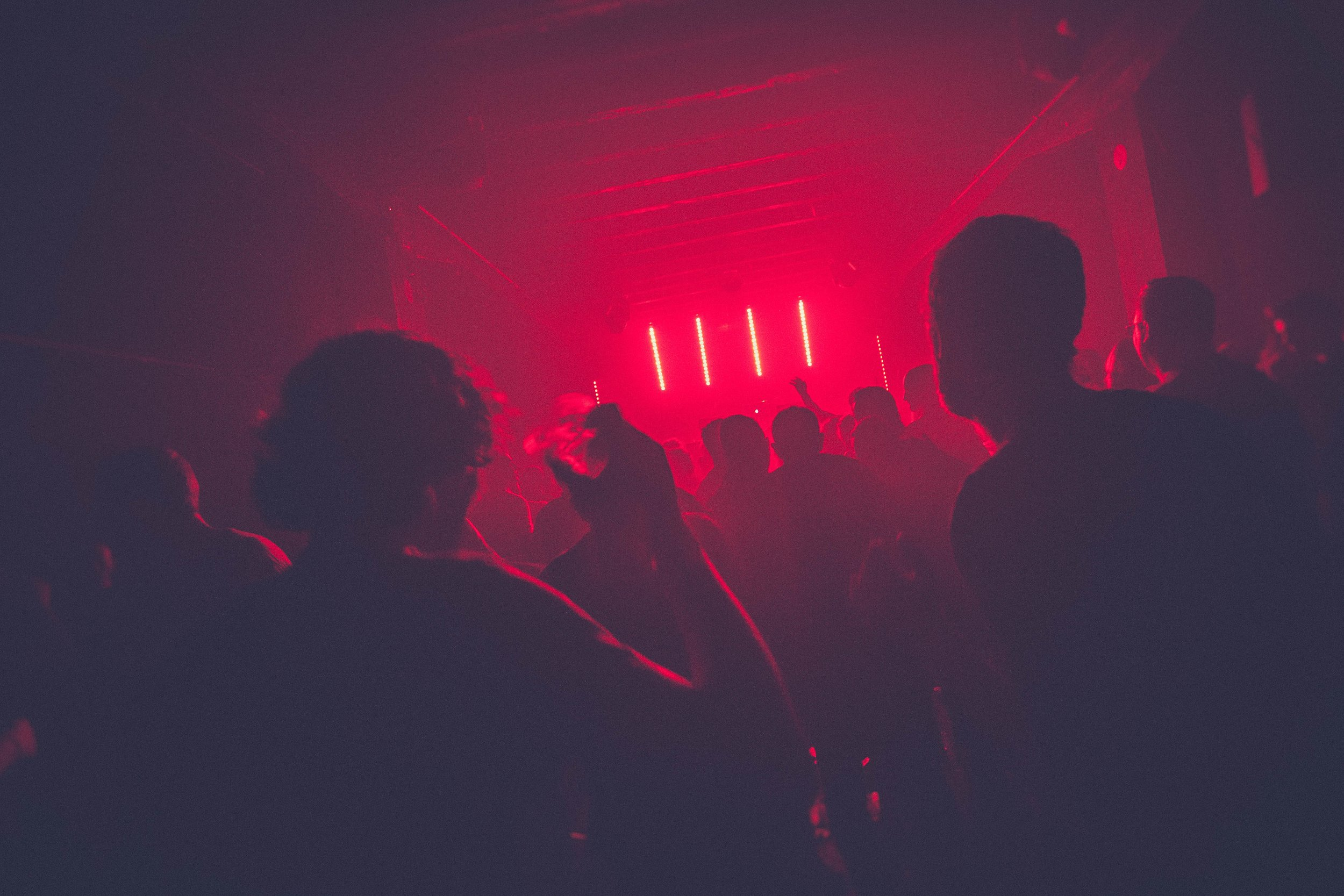 nightclub with dim red lighting filled with people