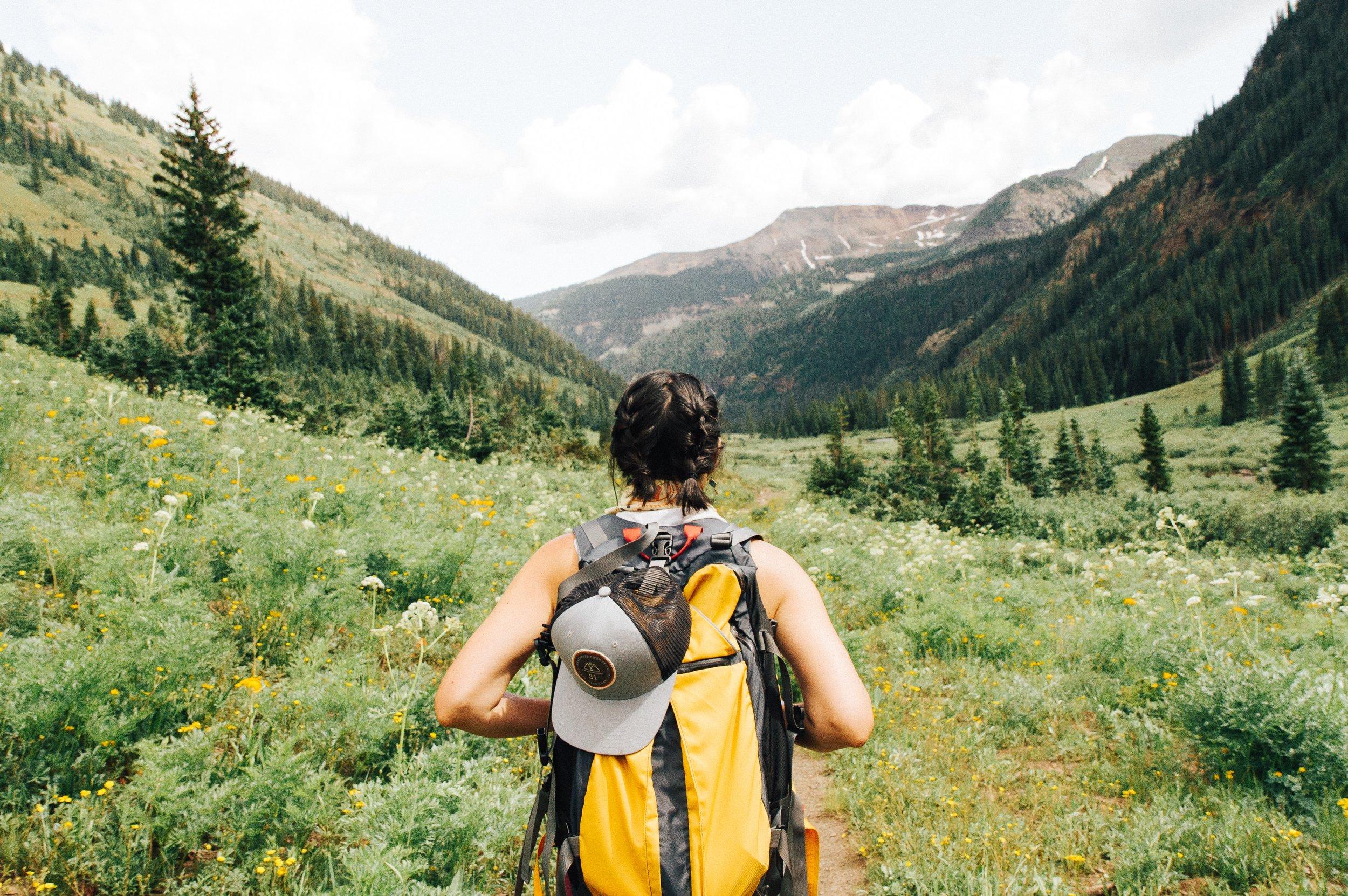 woman hiker walking through a green field between mountains
