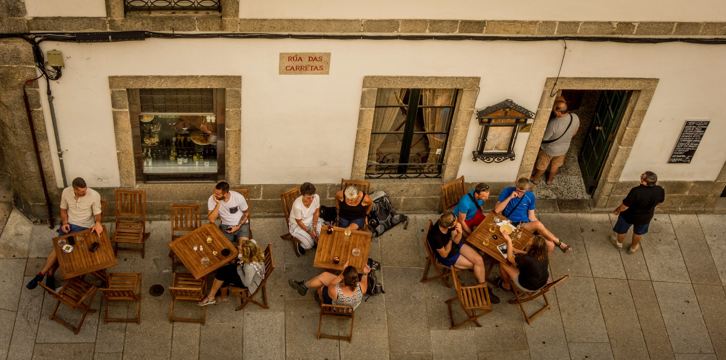 aerial shot of people sitting at tables at an outdoor cafe