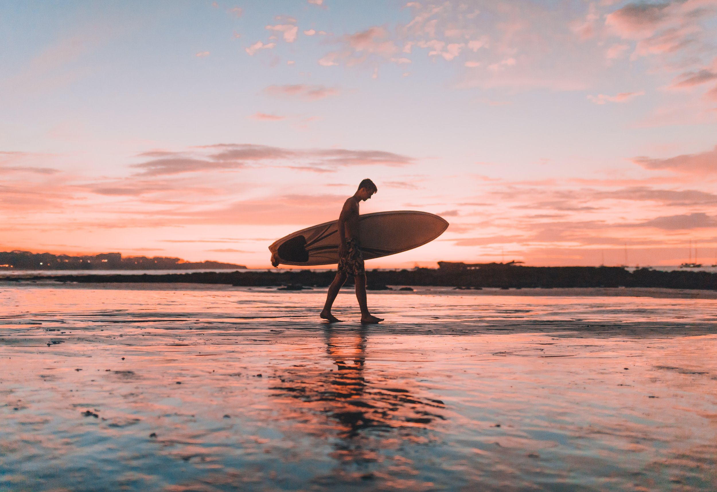 man walking with surfboard on the beach at sunset
