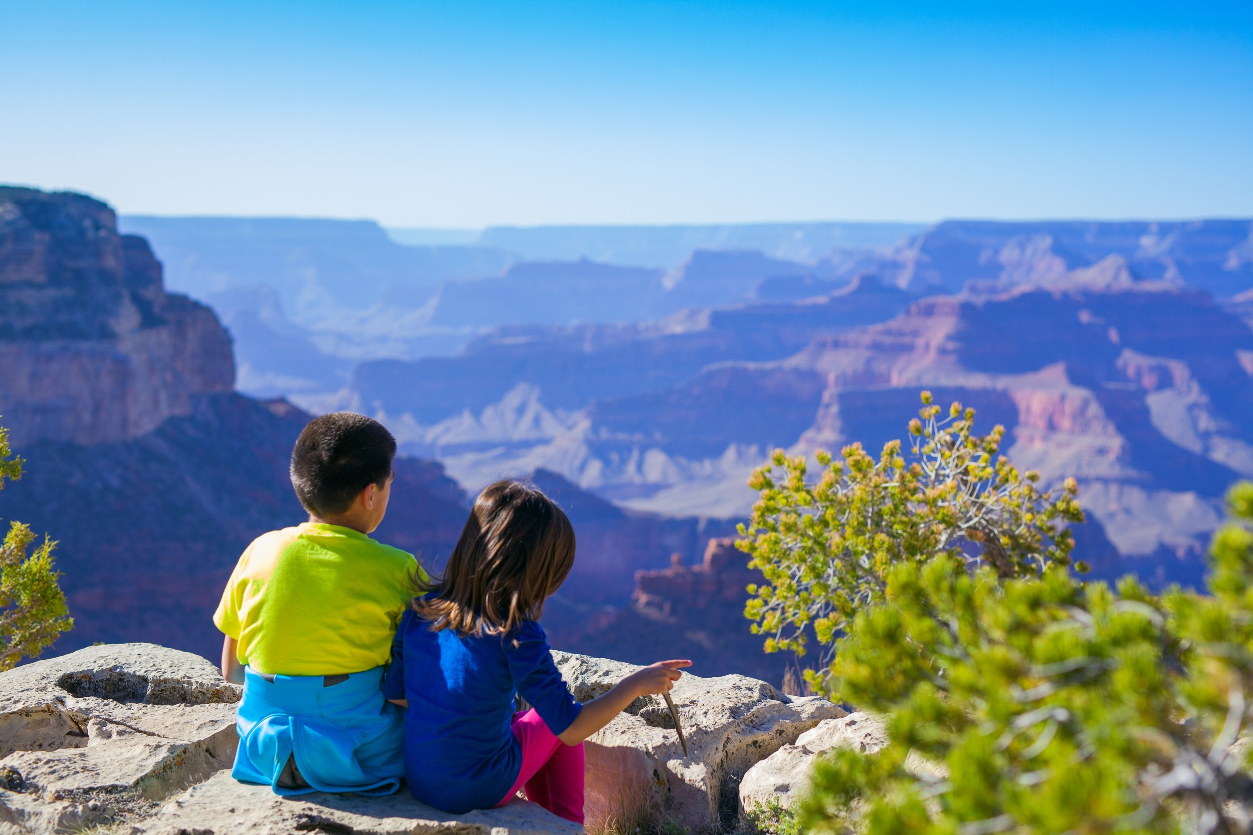two children sitting together while overlooking vast canyon