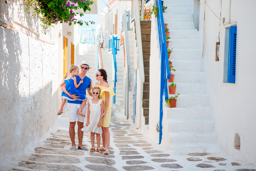 family with young children in the white streets of Greece