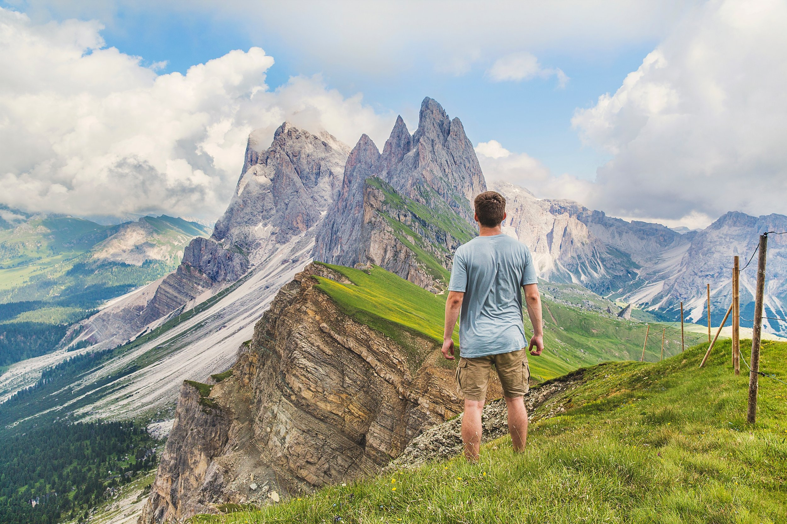 person looking at majestic mountains on a green hill