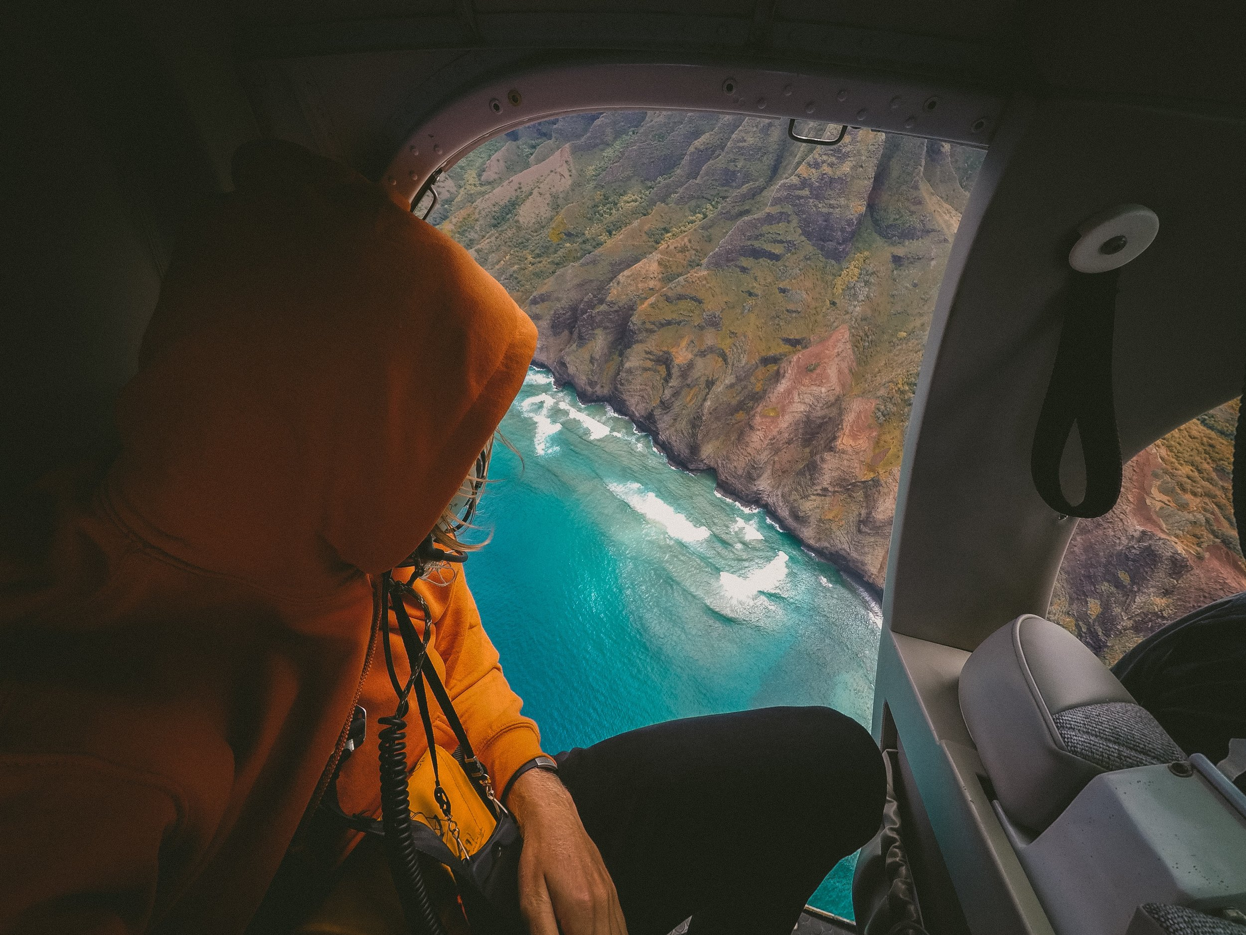 staring out the window of a helicopter at the sea and cliffside below