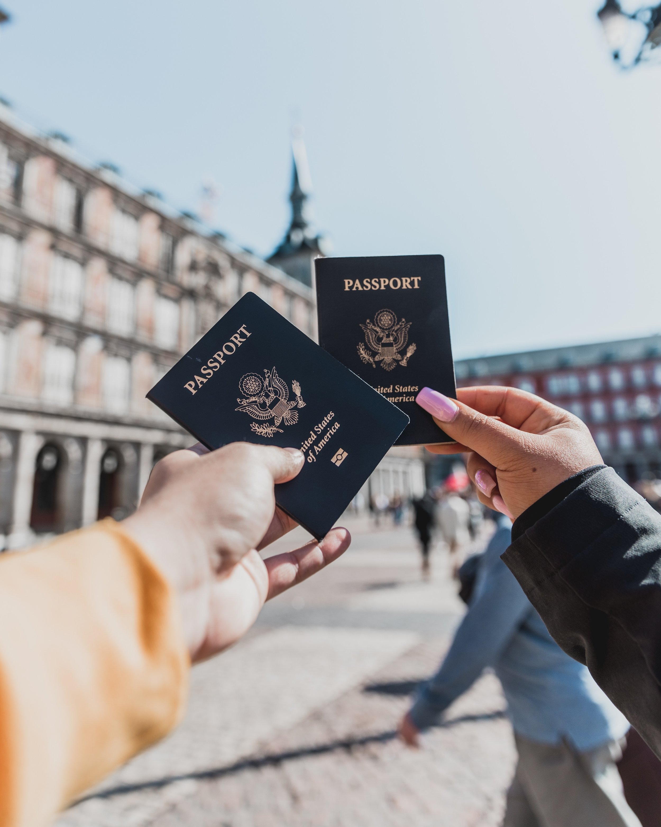 two people holding american passports with monuments in the background
