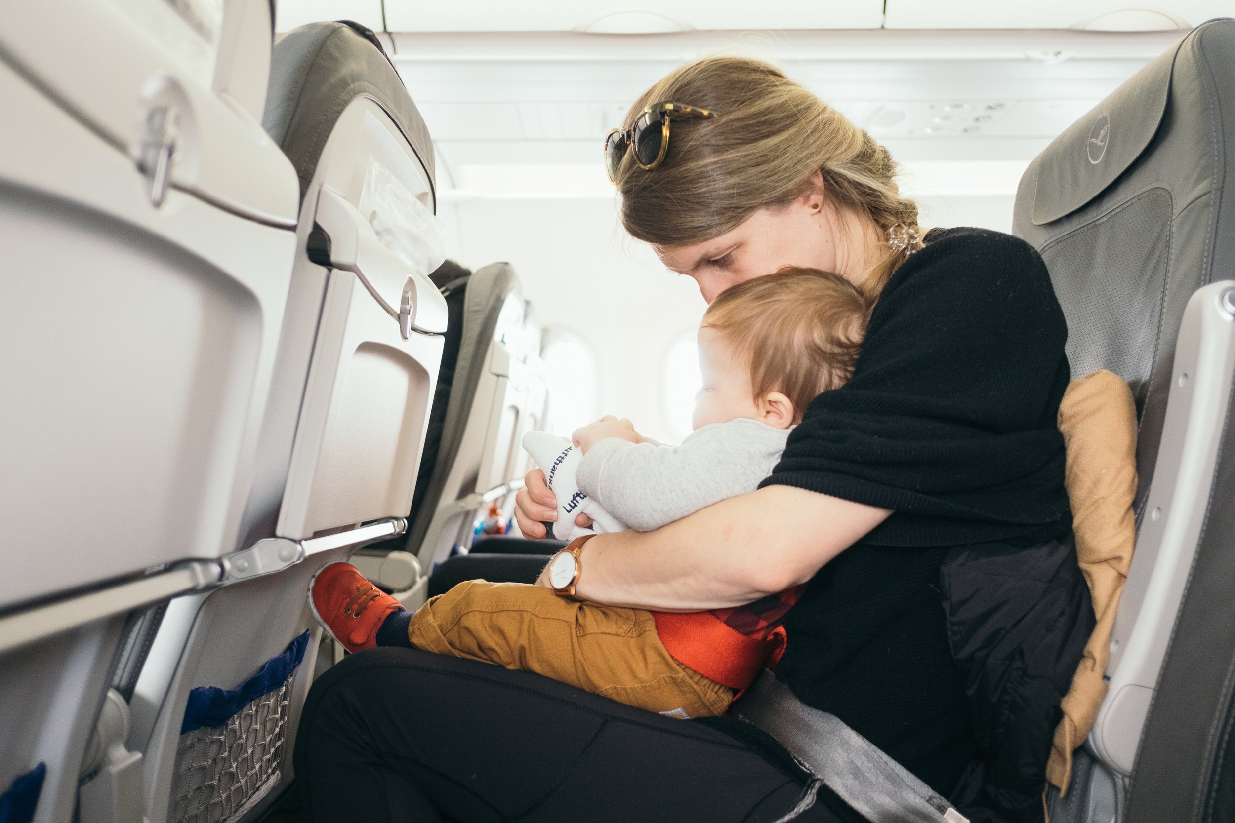 baby sitting on mothers lap on airplane