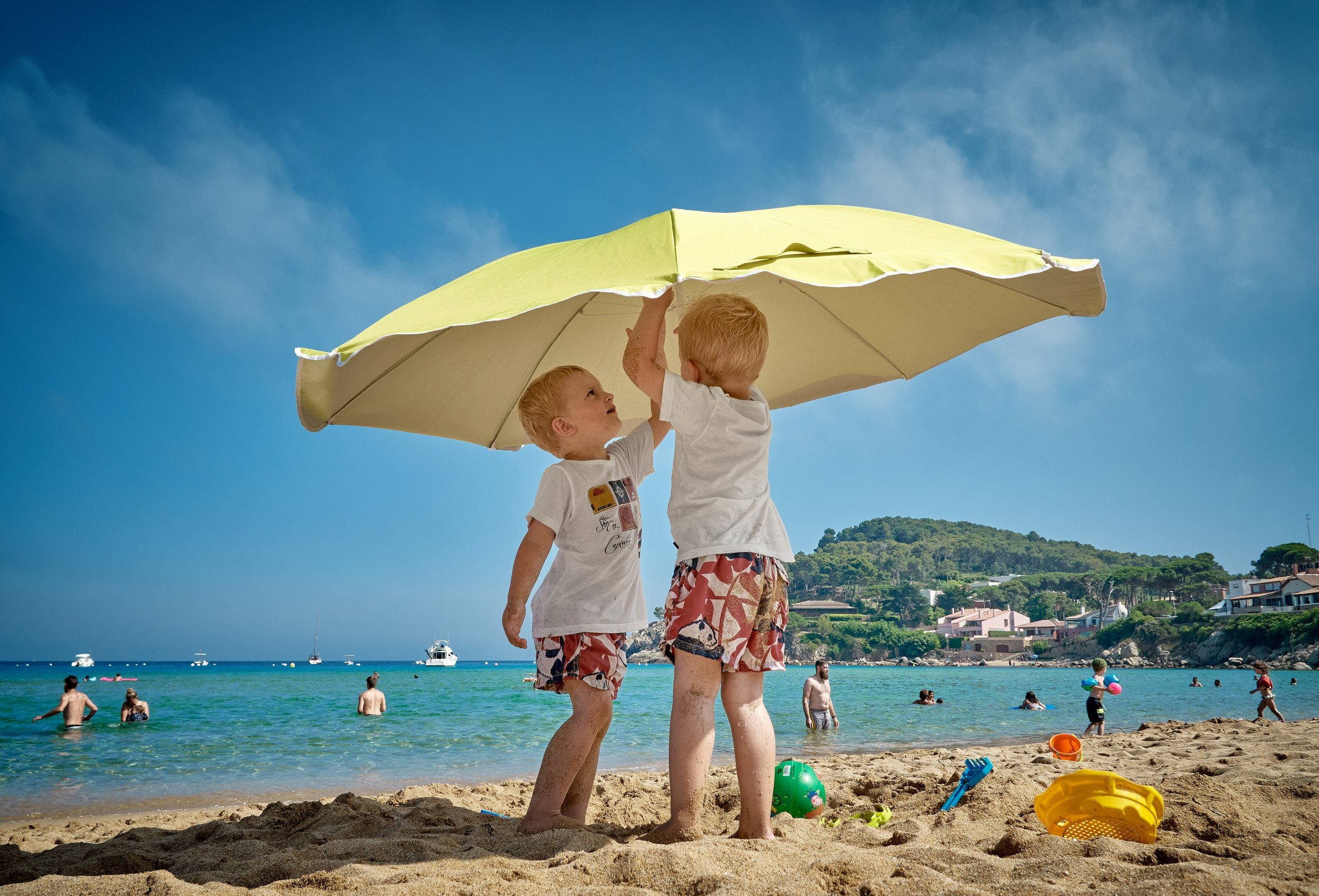 two children putting up umbrella on a sandy beach next to blue water