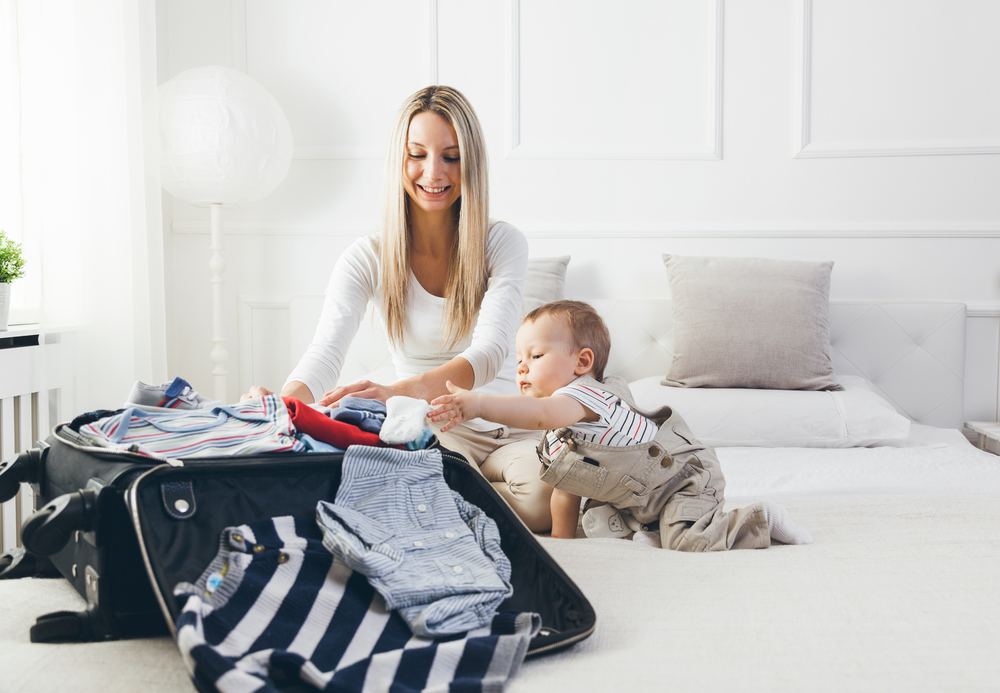 baby and mother packing a suitcase together