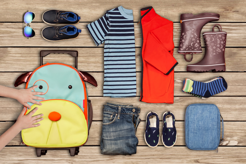 childrens clothing laid out for packing in backpack