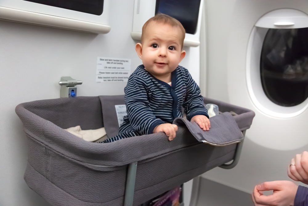 baby sitting in bassinet on airplane