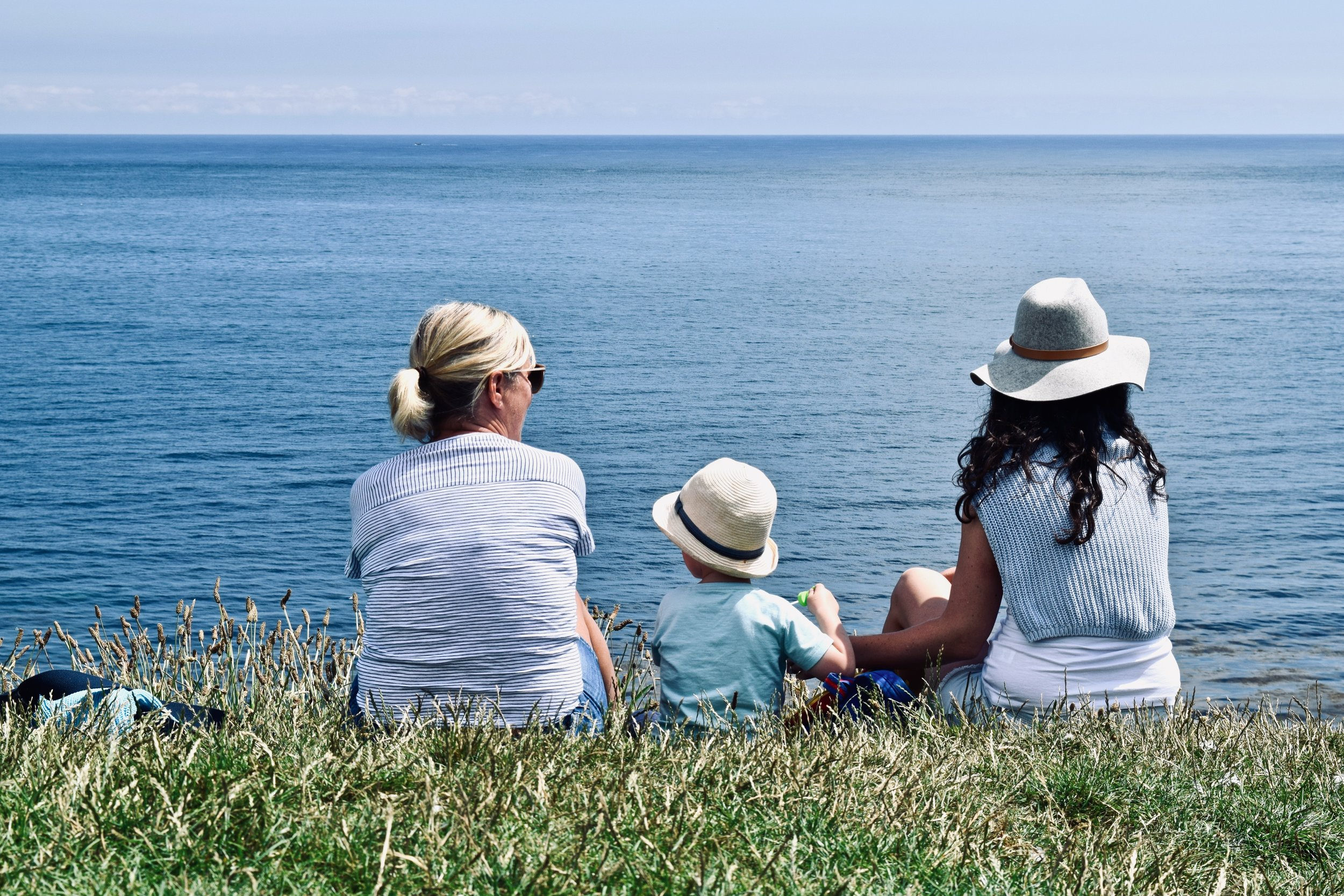 two adults and one small child sitting on the grass overlooking the ocean