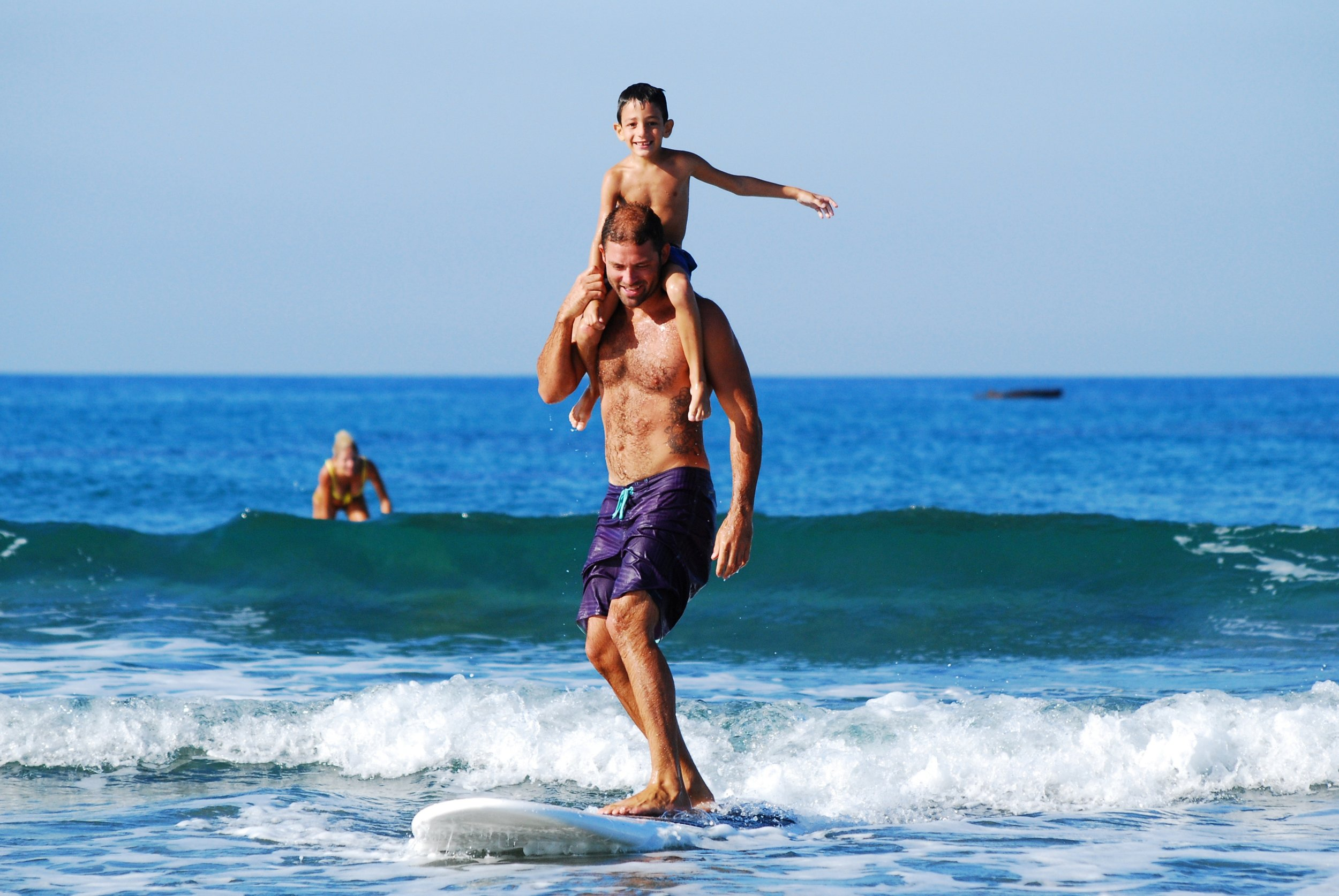child sitting on fathers shoulders while surfing a small wave