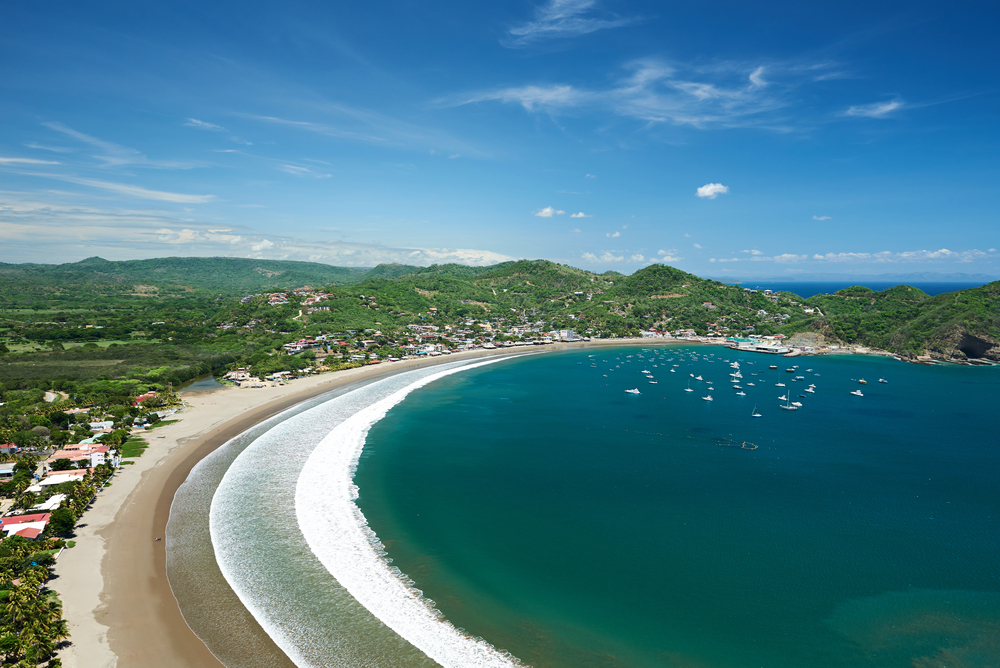 aerial view of san juan del sur beach with green hills in the background