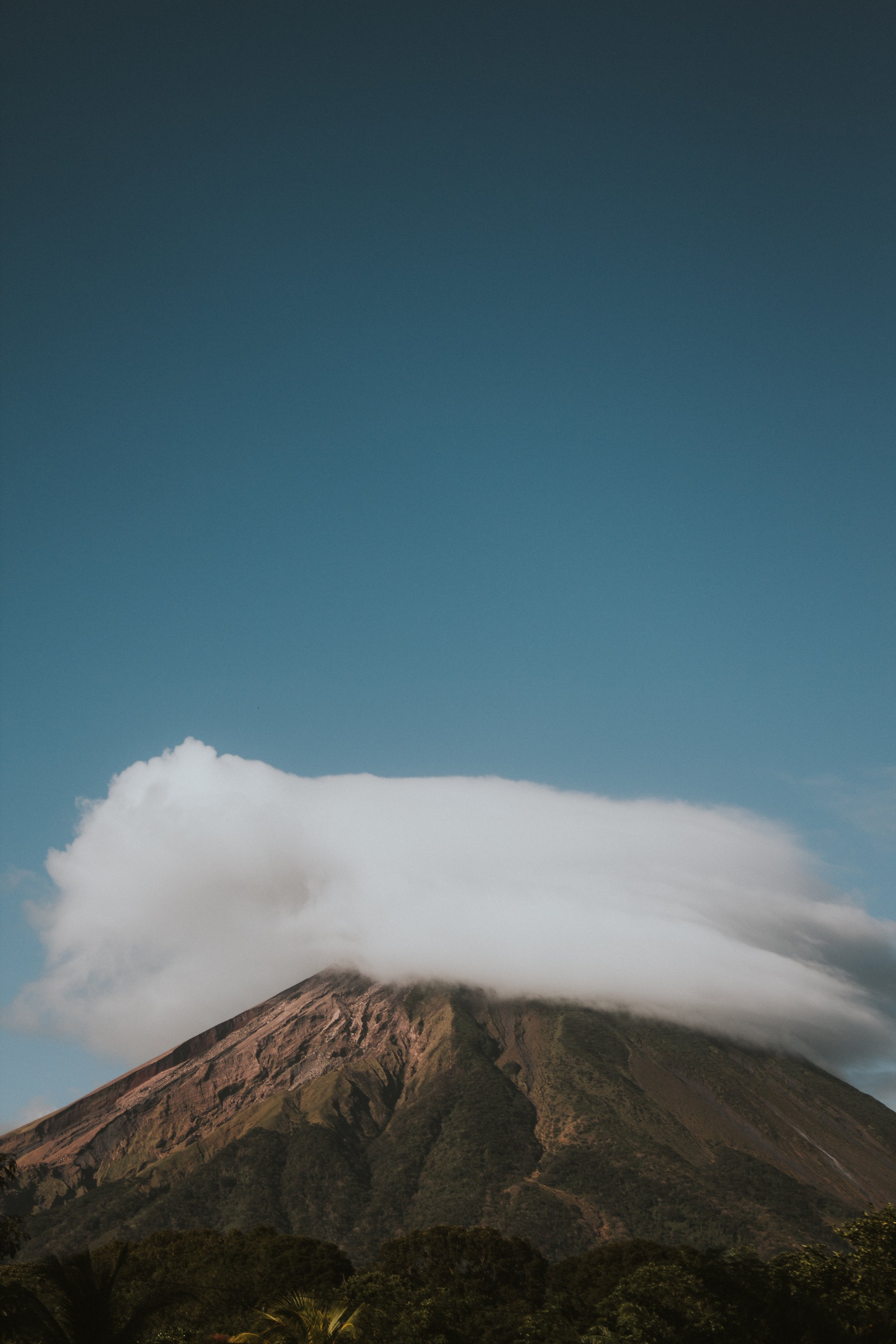volcano shrouded in white clouds against a blue sky background