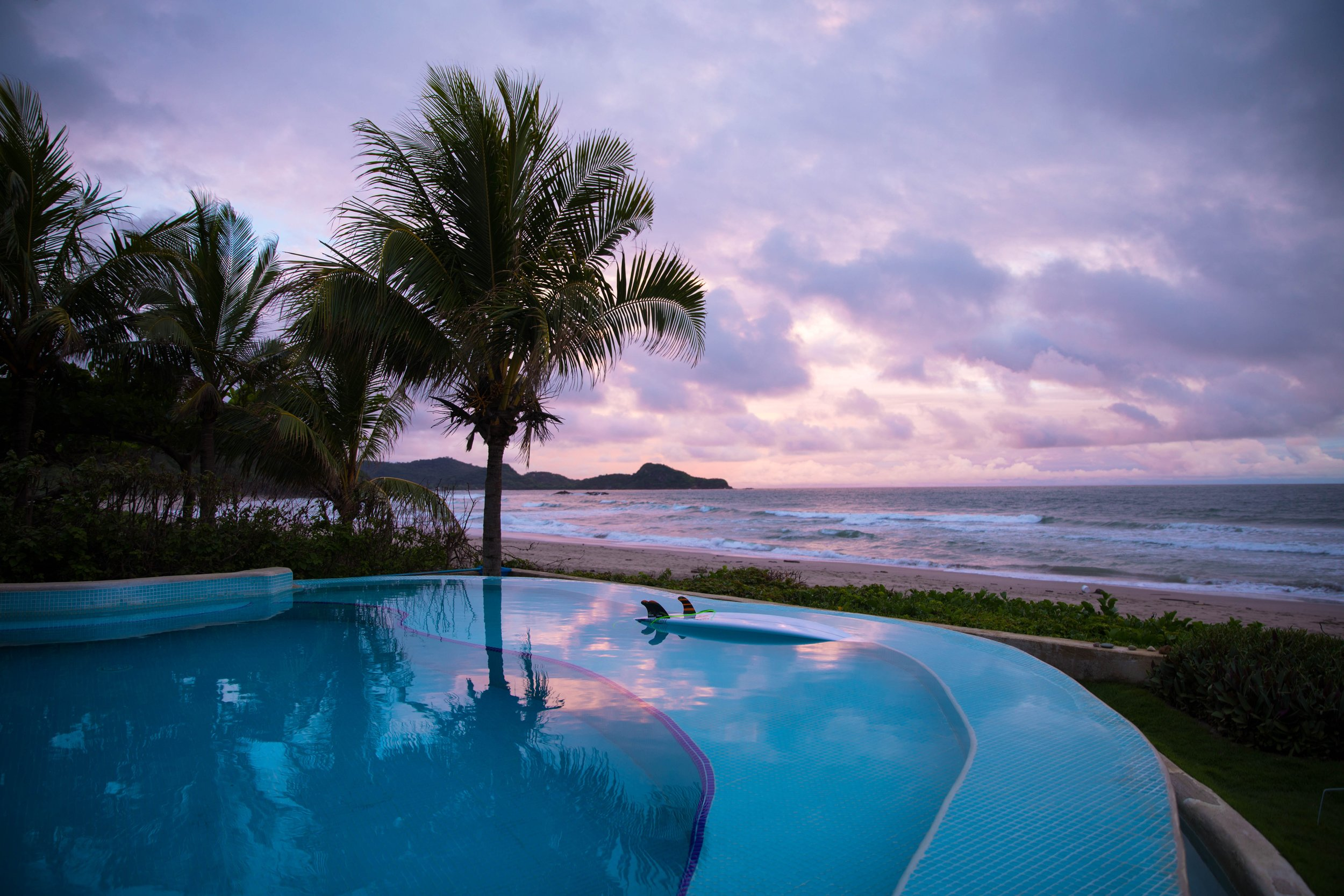 infinity pool next to the beach with a pink and purple sunset