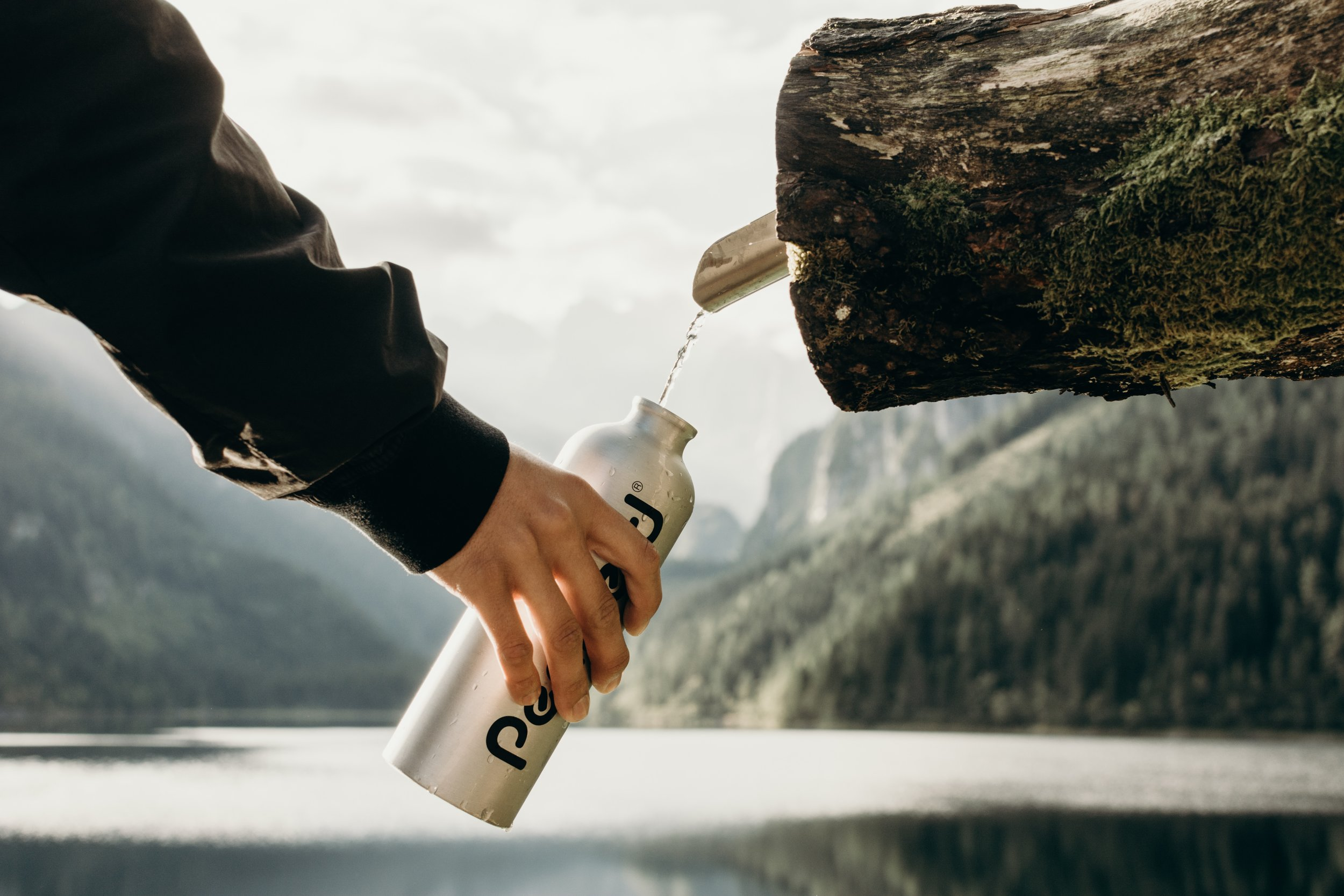 reusable water bottle being refilled outside