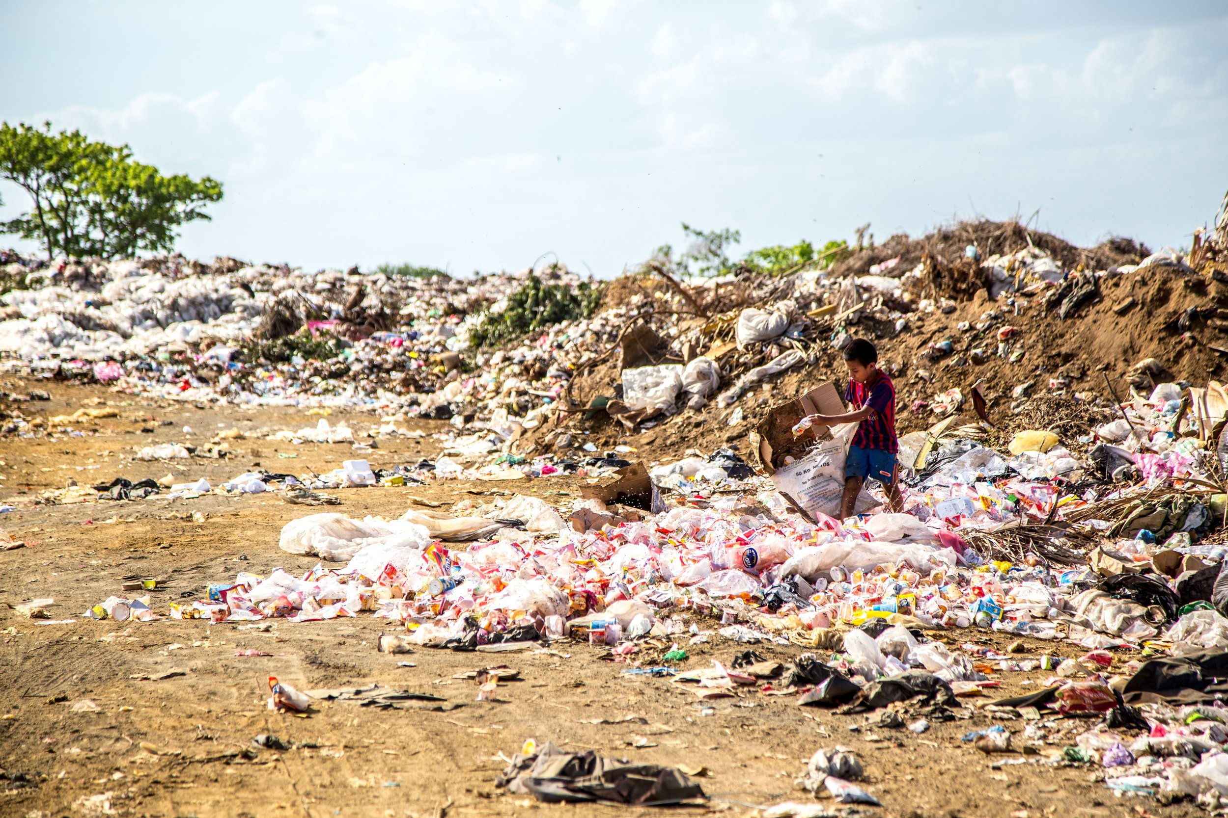 person surrounded by plastic waste in the countryside