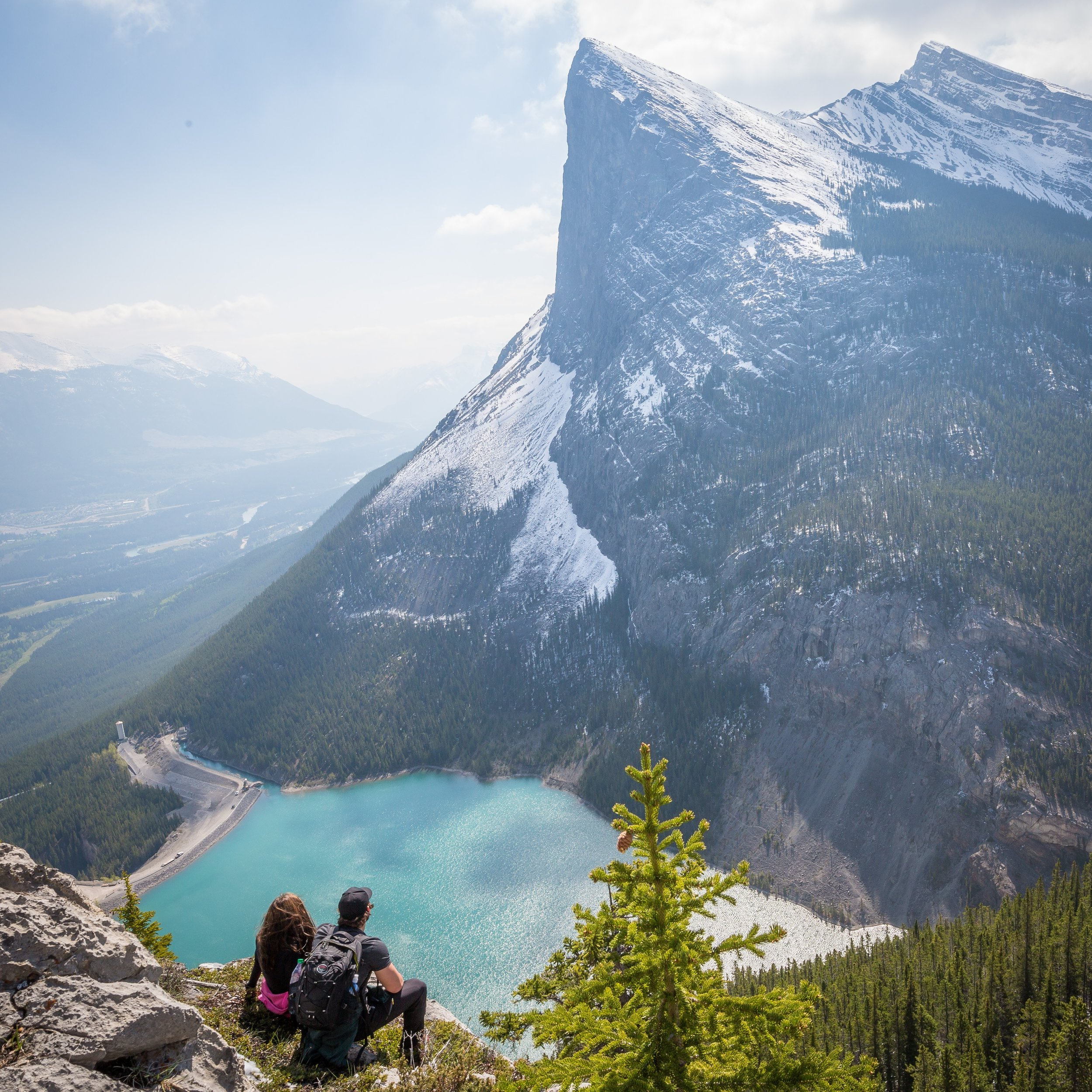 two hikers sitting on a peak overlooking turquoise lake and mountains