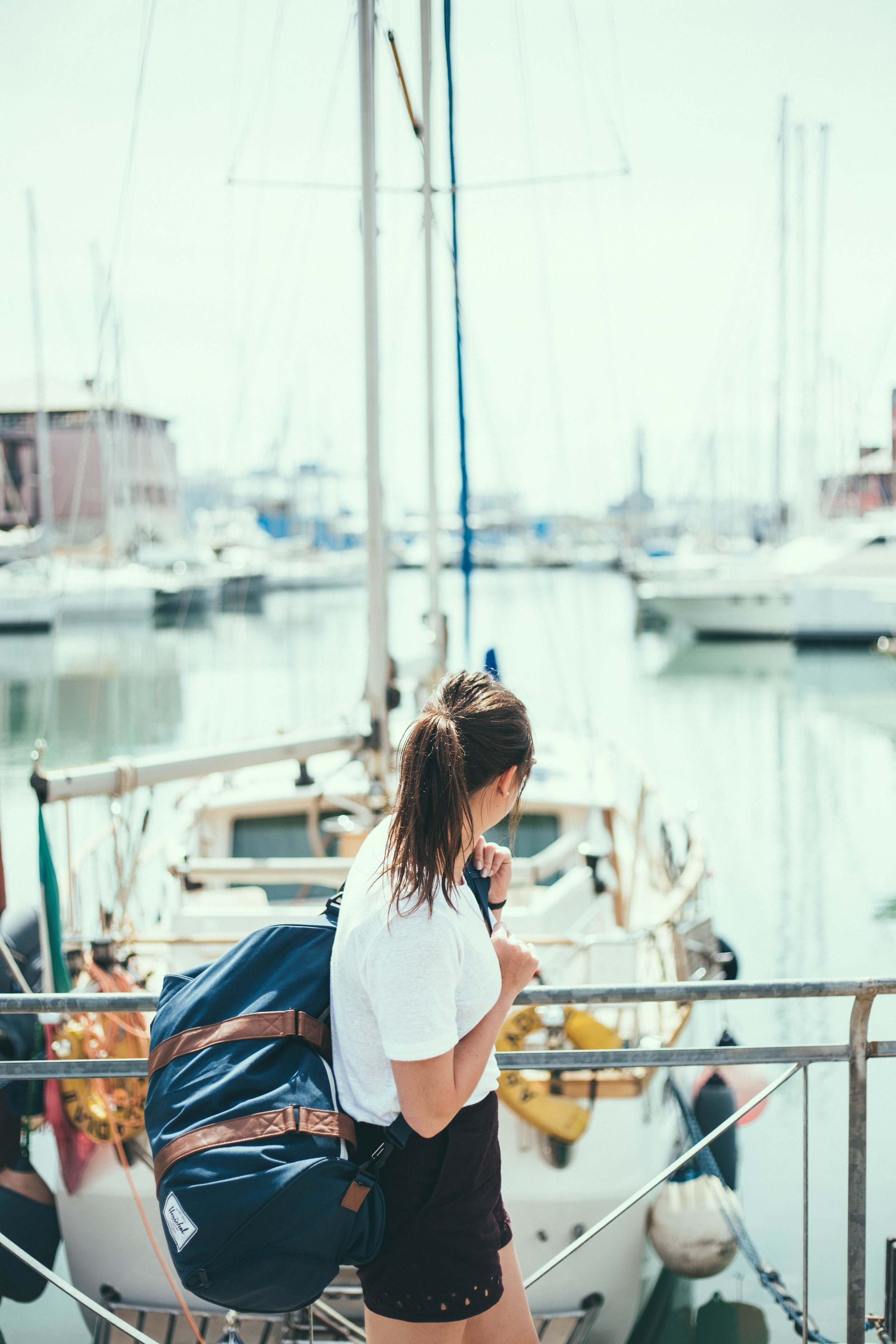 woman at dock with suitcase about to board a boat