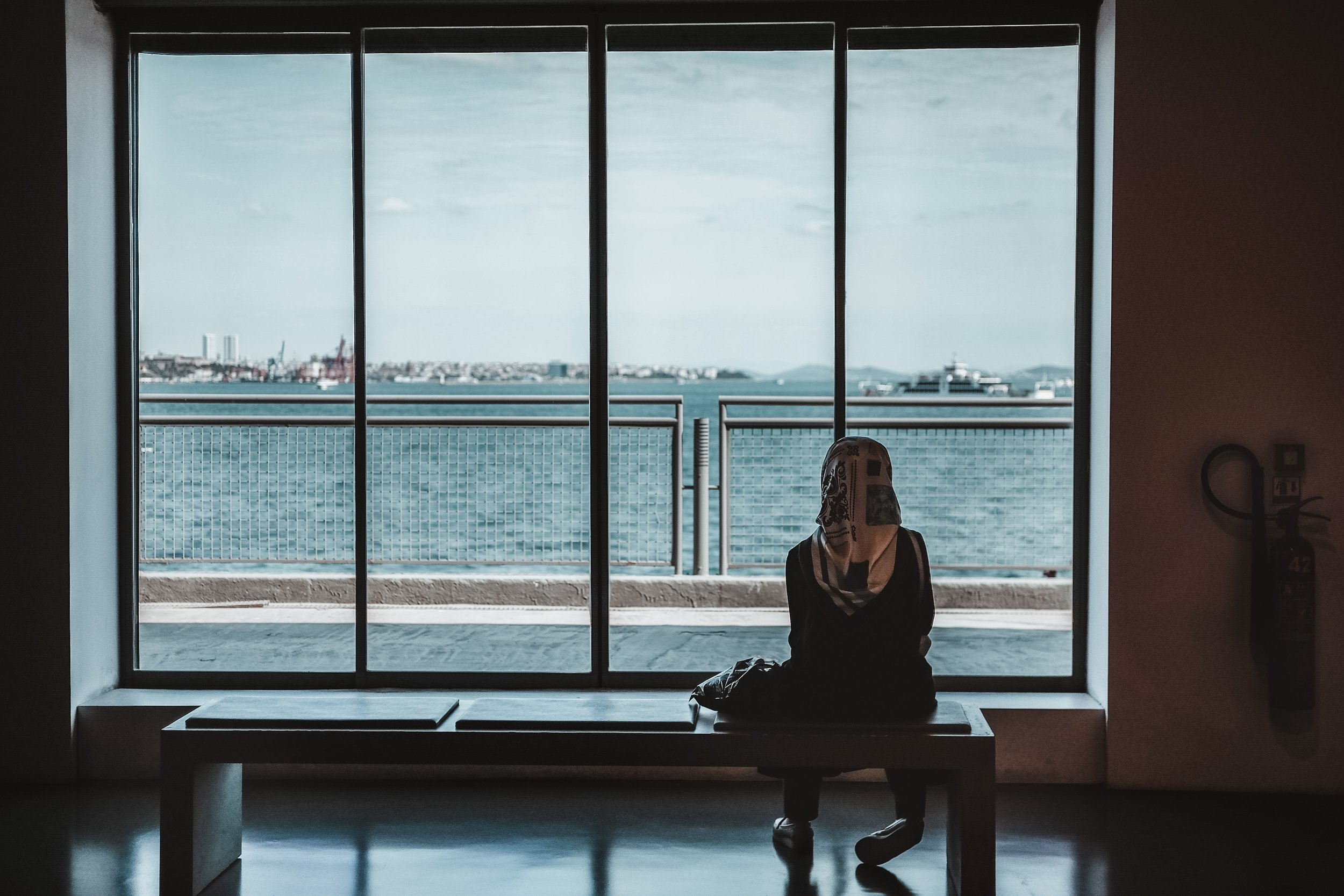woman sitting at airport looking out the window