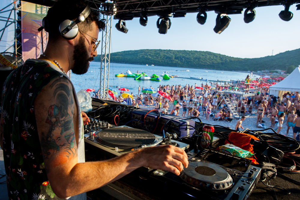 dj playing to crowd next to the water