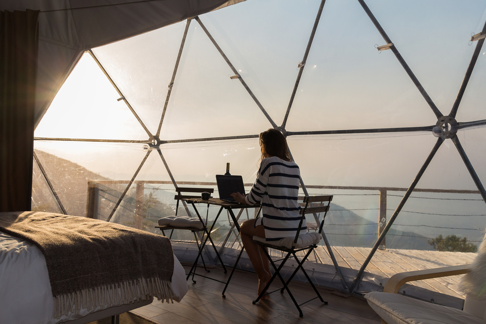 glamping set up overlooking the water with woman sitting at table