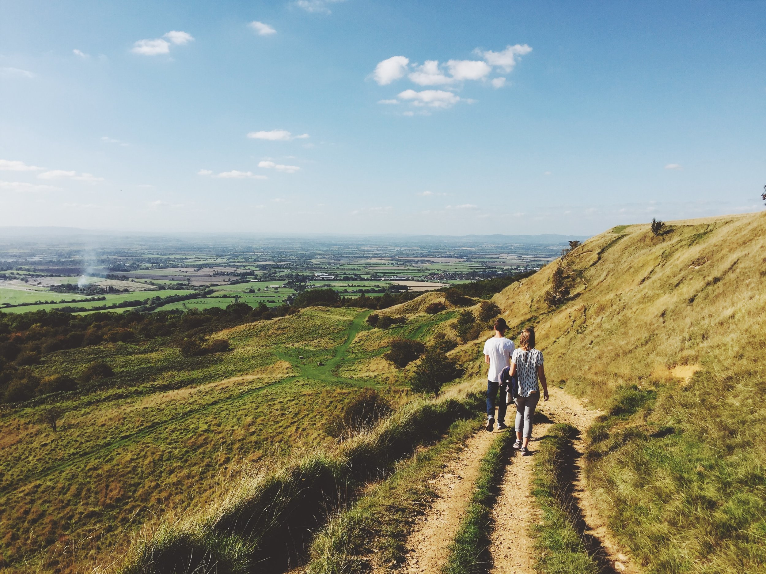 couple walking through open grasslands