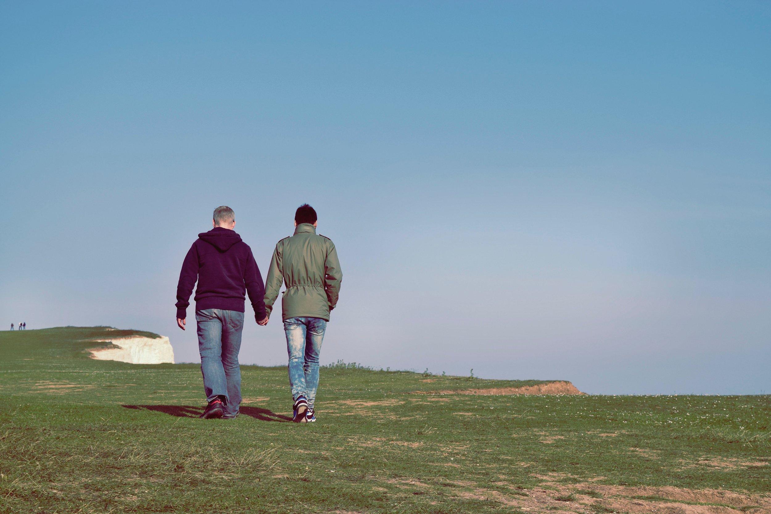 couple holding hands walking through grass