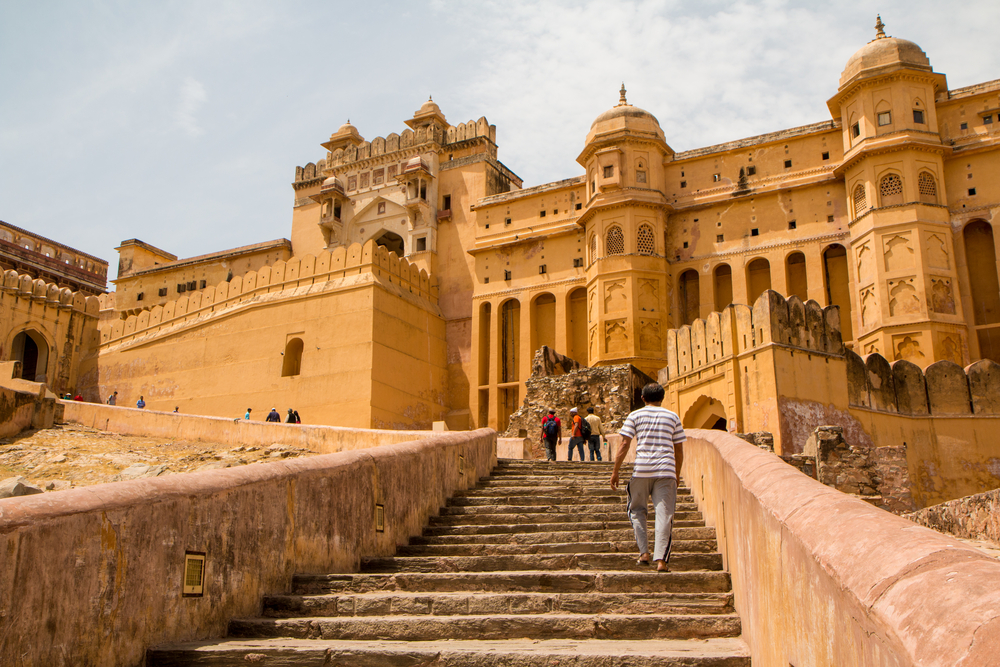 yellow indian palace with stairs leading up to the door