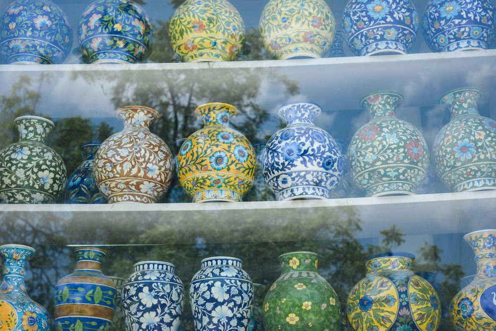 colorful ceramic pots lined up in a shop window