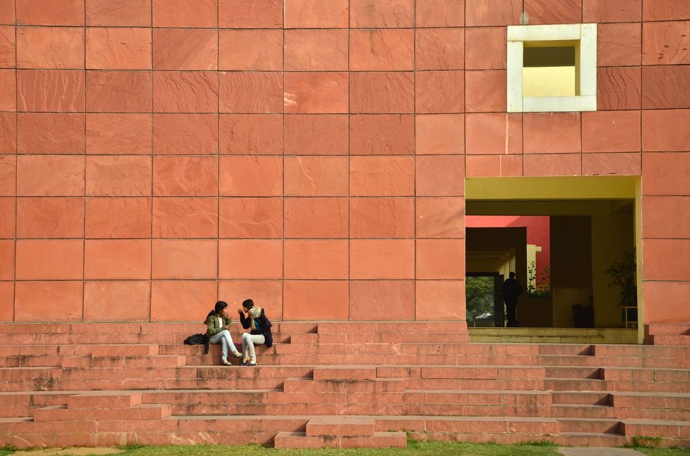 two people sitting on the red steps of an arts center