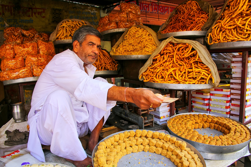 man serving traditional indian street food
