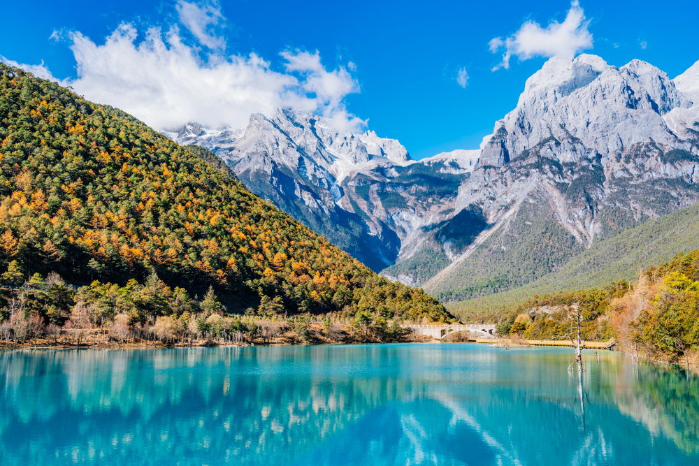 crystalline lake with towering snow capped mountains and forested hills