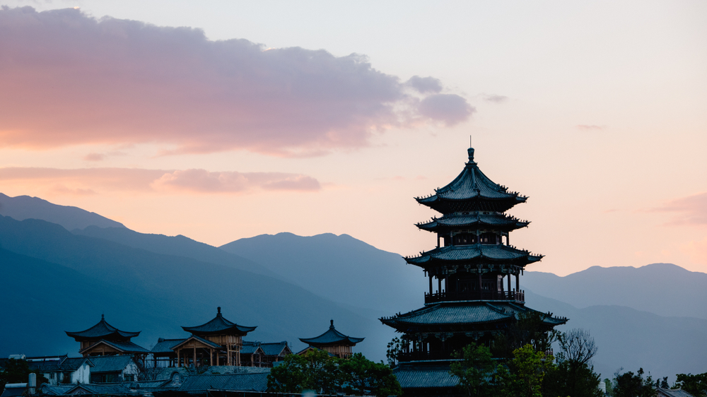 tiered temple with mountains and sunset in the background